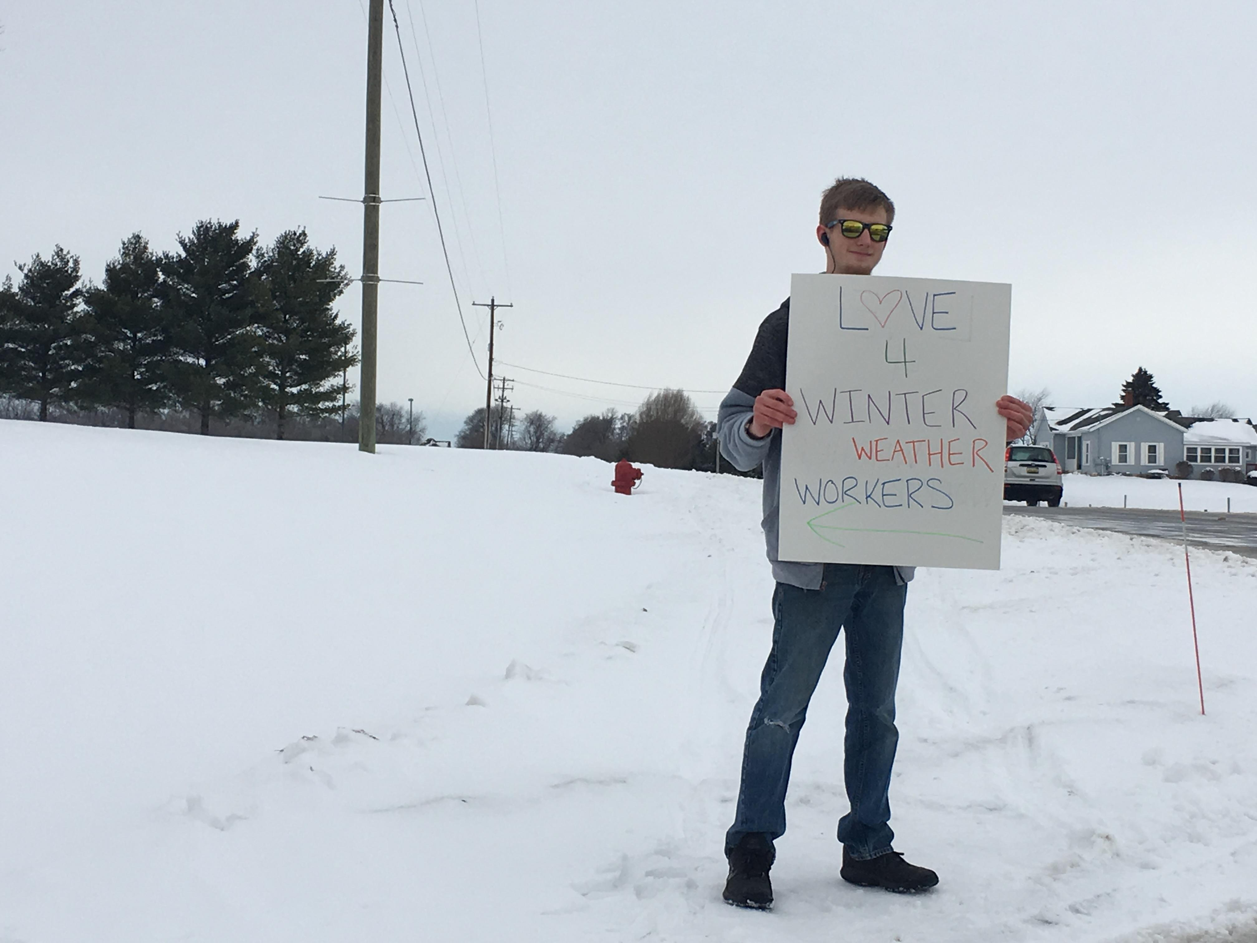 A Thornapple Kellogg High school student holds a sign up to attract workers serving the community to their drive up treat drop off.{ } Feb. 14, 2019.{ } (WWMT/ Will Haenni)