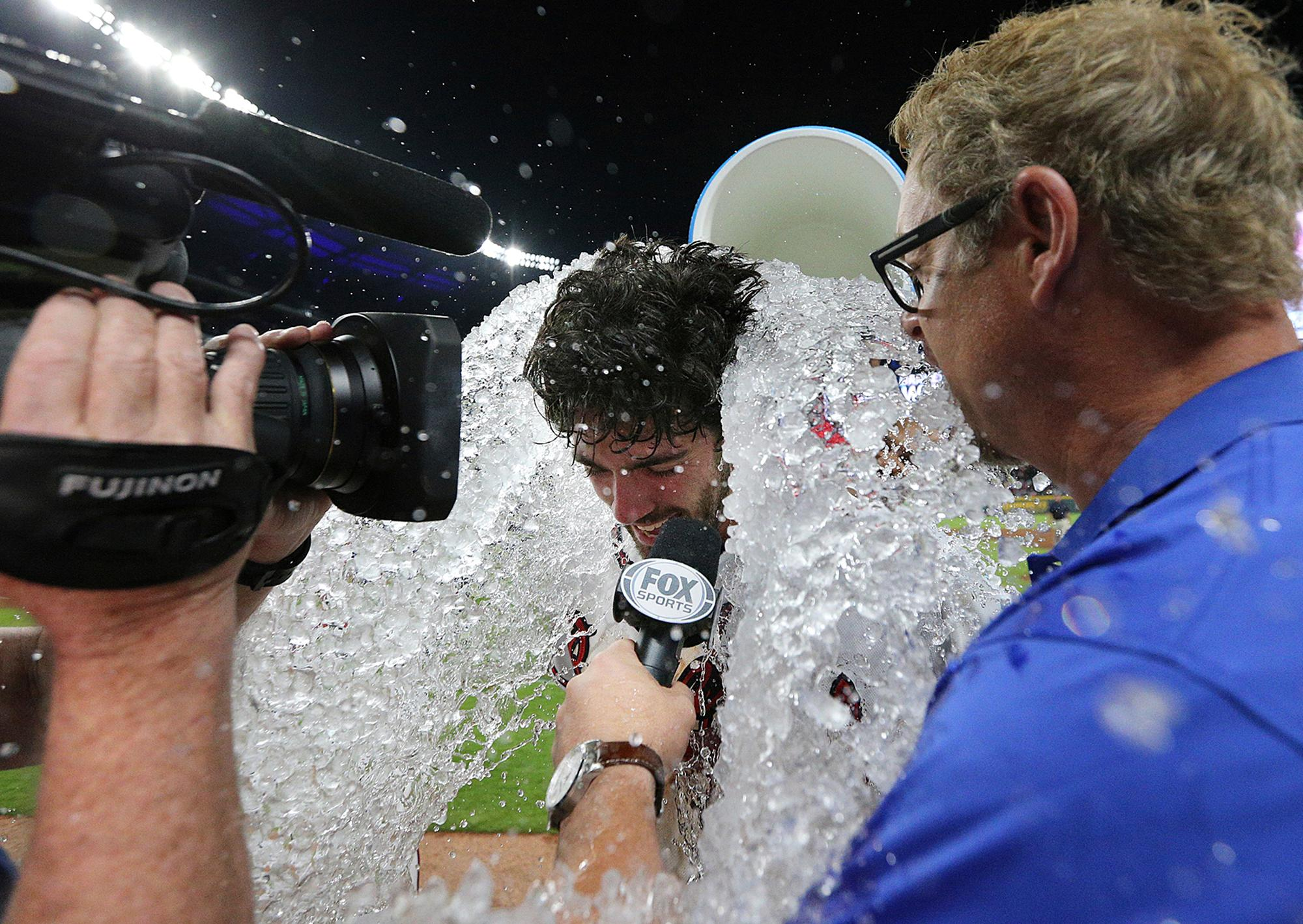 Adonis Garcia douses Atlanta Braves' Dansby Swanson with water to celebrate his walk-off single to beat the San Diego Padres, 5-4, at  the end of a baseball game in Atlanta on Monday, April 17, 2017. (Curtis Compton/Atlanta Journal-Constitution via AP)