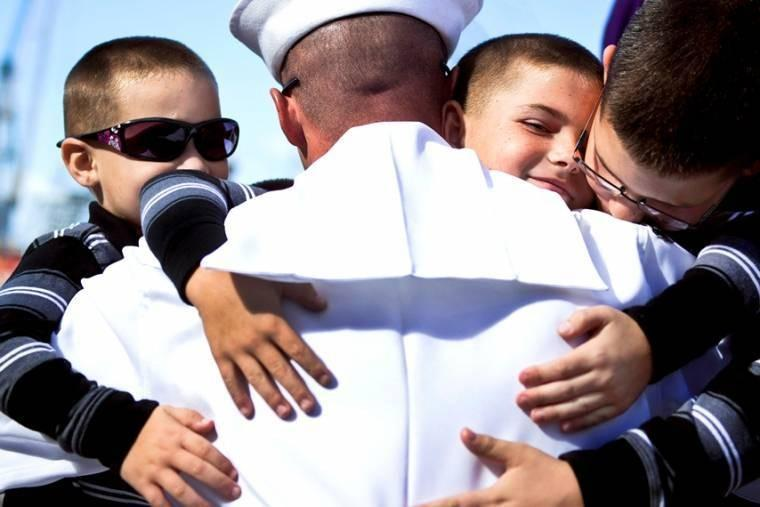 Navy Petty Officer Engineman 1st Class Kevin Ives, assigned to the guided-missile cruiser USS Princeton, embraces his sons during a homecoming celebration on Naval Base San Diego.
