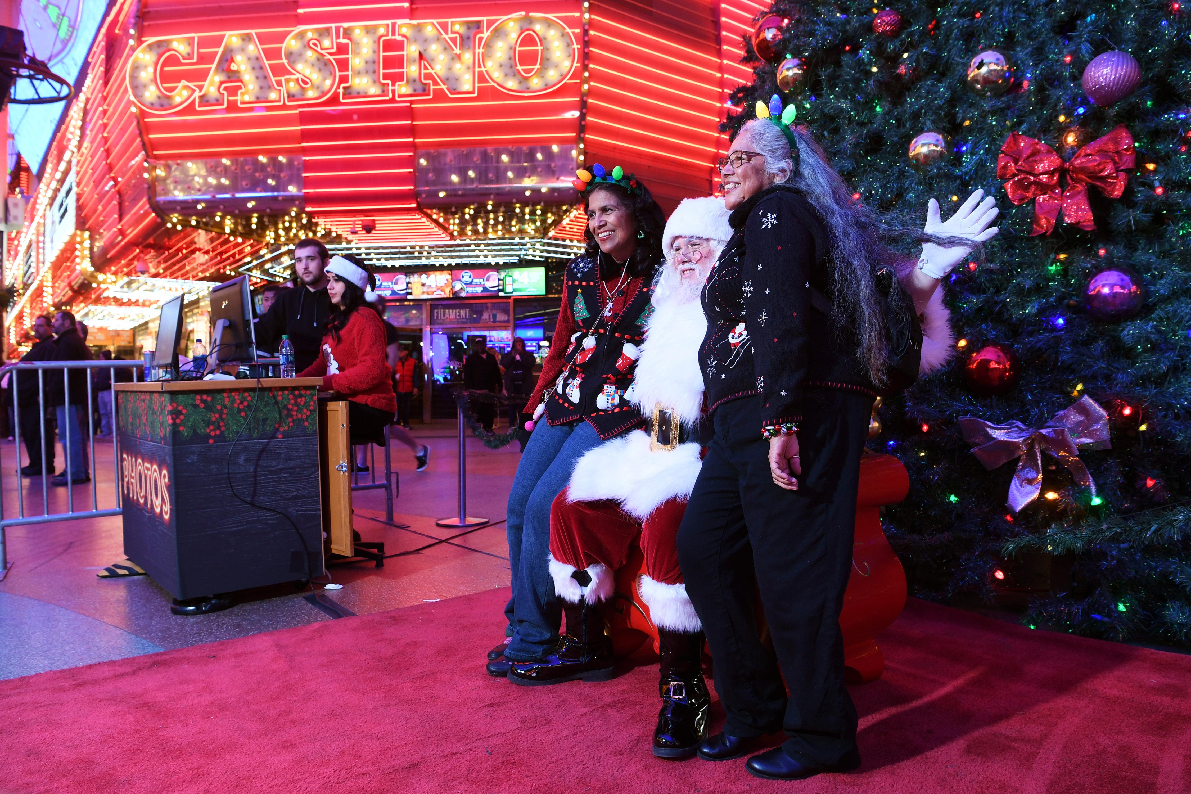 Armida Mejia, left, and Chachi Mejia have their photo taken with Santa during the annual lighting of a Christmas tree at the Fremont Street Experience Tuesday, December 4, 2018. CREDIT: Sam Morris/Las Vegas News Bureau
