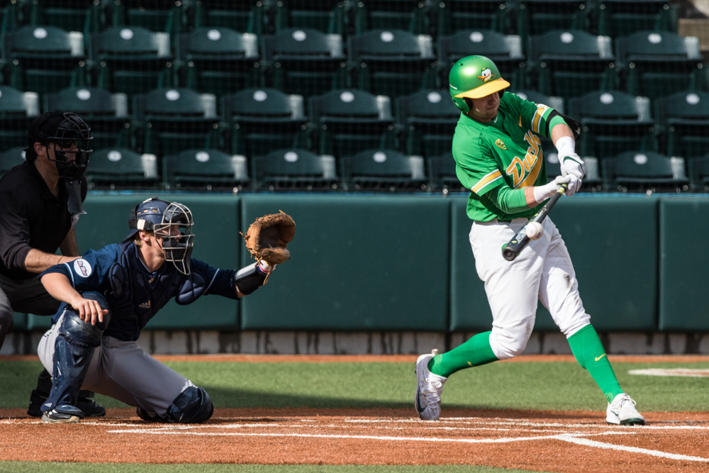 Oregon Ducks infielder Spencer Steer (#13) hits a pitch against UC Irvine. Oregon Ducks pitcher Matt Mercer (#11) throws a pitch.  In the second of the three game series, the Ducks beat the UC Irvine Anteaters 6-3. Photo by Austin Hicks, Oregon News Lab