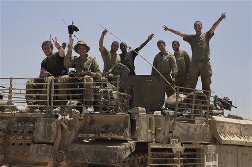Israeli soldiers give the victory sign on the top of armored vehicle near the Israel Gaza border.