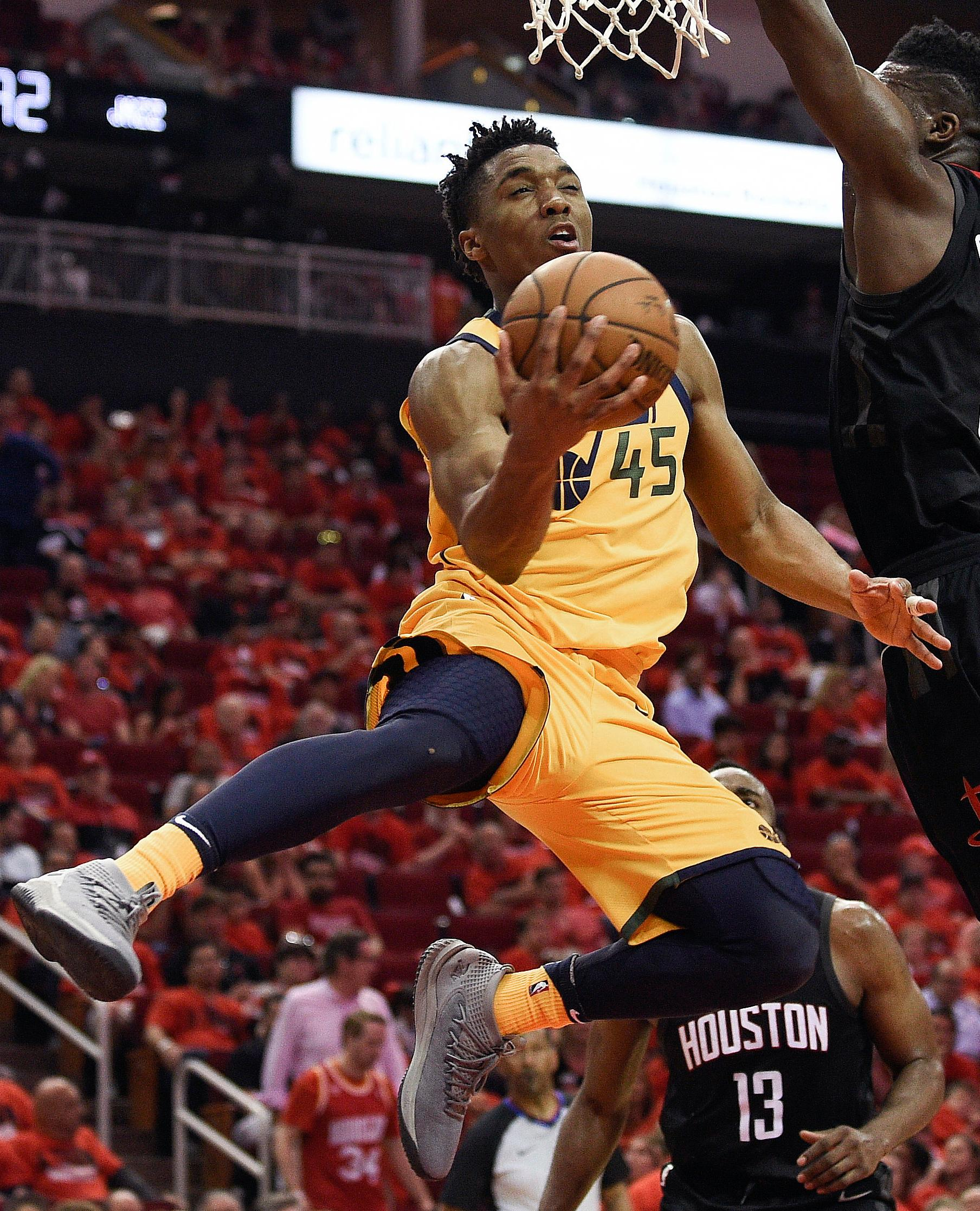 Utah Jazz guard Donovan Mitchell (45) drives to the basket as Houston Rockets center Clint Capela, right, defends during the second half in Game 1 of an NBA basketball second-round playoff series Sunday, April 29, 2018, in Houston. (AP Photo/Eric Christian Smith)