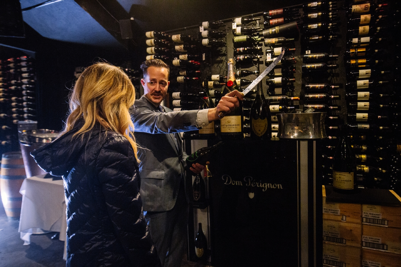 Champagne sabering at the Bearfoot Bistro takes place in their wine cellar, where they house over 20,000 bottles of wine. (Image: Joshua Lewis / Seattle Refined)