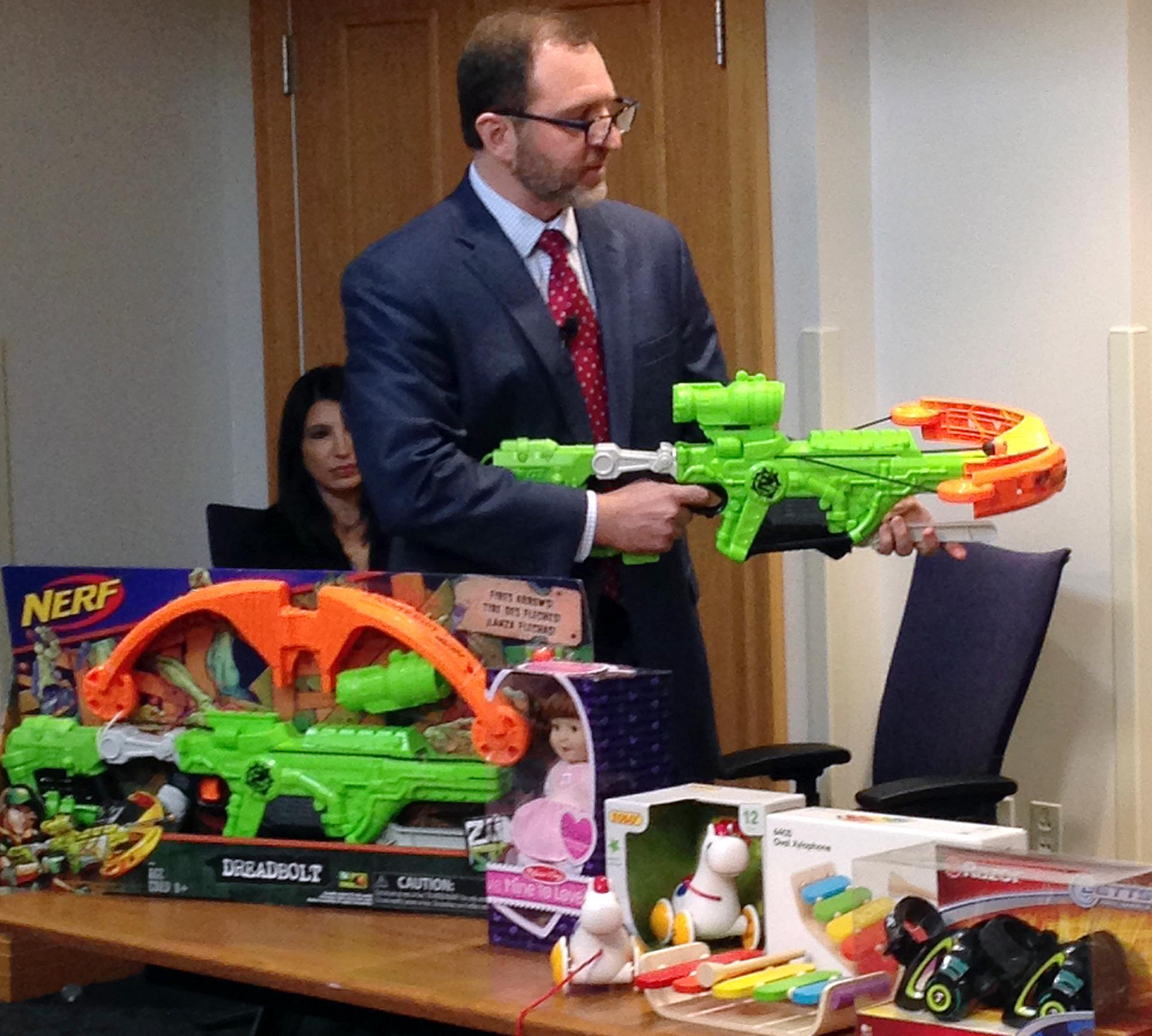 "James Swartz, director of World Against Toys Causing Harm, or W.A.T.C.H., displays Nerf's ""Zombie Strike"" crossbow during a news conference Tuesday, Nov. 14, 2017, in Boston, where the child safety group released its annual holiday list of the 10 most hazardous toys. (AP Photo/Philip Marcelo)"