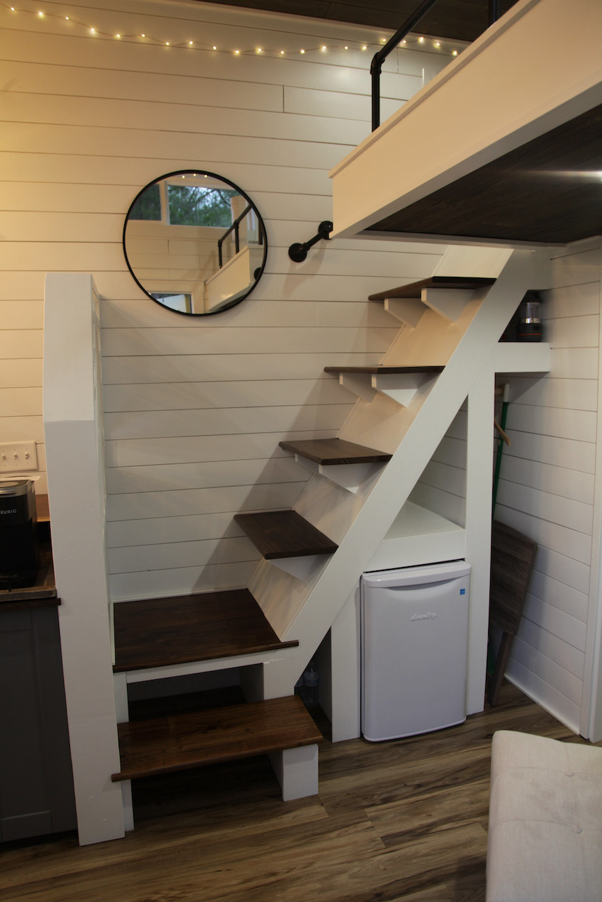 The stairs leading to the loft in the Trillium tiny house with the refrigerator below and a small closet space to the right / Image: Chez Chesak{ }// Published: 1.24.21