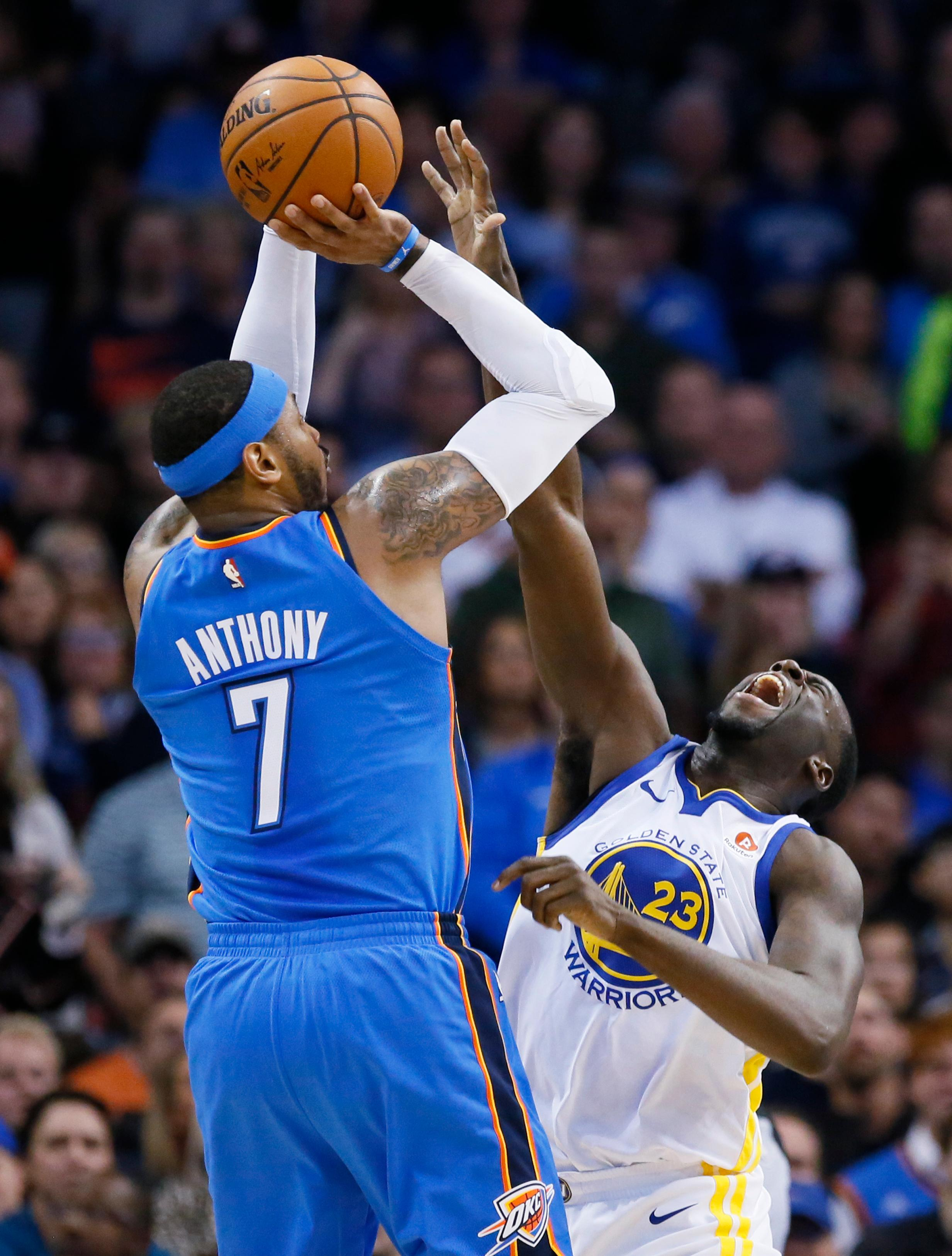 Oklahoma City Thunder forward Carmelo Anthony (7) shoots over Golden State Warriors forward Draymond Green (23) during the first quarter of an NBA basketball game in Oklahoma City, Wednesday, Nov. 22, 2017. (AP Photo/Sue Ogrocki)