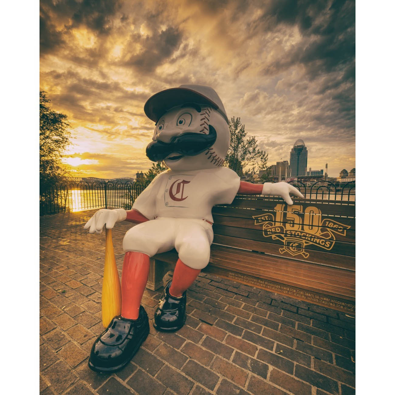 To celebrate the Reds' 150th Anniversary, 24 benches featuring Mr. Redlegs sculptures have been added to various spots around the area, as well as out of town locations including Dayton, Loveland, and Louisville, for the perfect Reds photo op. The mascot sports different uniforms from throughout the team's history at each of the benches. The Reds have been wearing these same throwback uniforms during their 2019 season. / Location:{ }Historic Licking Riverside Drive in Covington / Uniform: 1869 / Image courtesy of Instagram user @jonreynoldsphoto    // Published: 5.14.19
