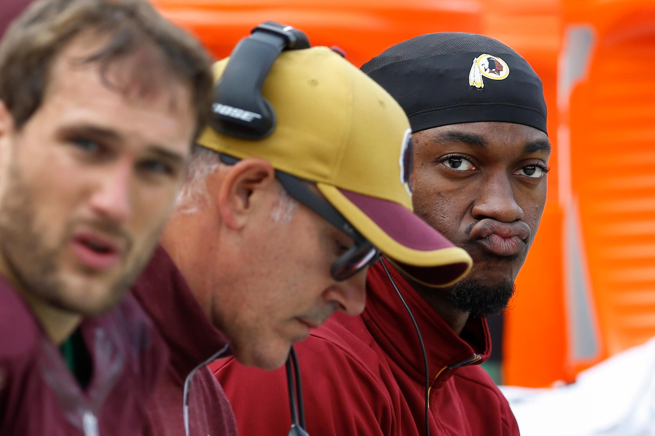 Washington Redskins quarterback Robert Griffin III (10) watches the action from the bench during the first half of an NFL football game against the Tampa Bay Buccaneers in Landover, Md., Sunday, Oct. 25, 2015. (AP Photo/Patrick Semansky)