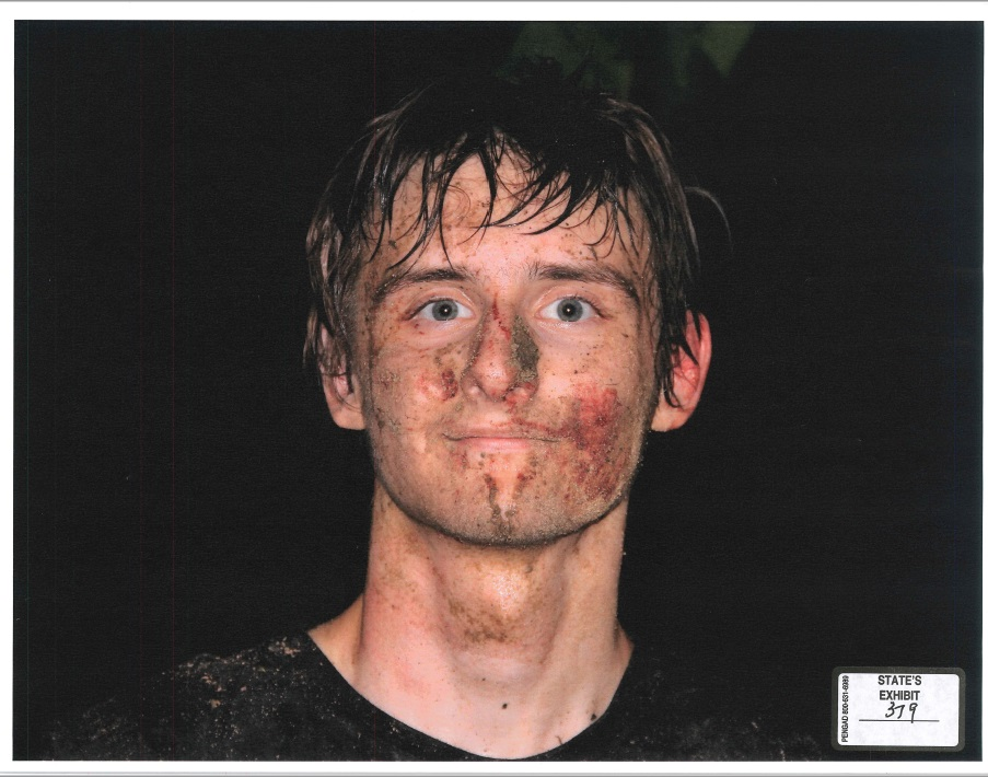 A close-up photograph of Robert Bever's blood-smeared face after his arrest for killing his parents and three siblings. (KTUL)