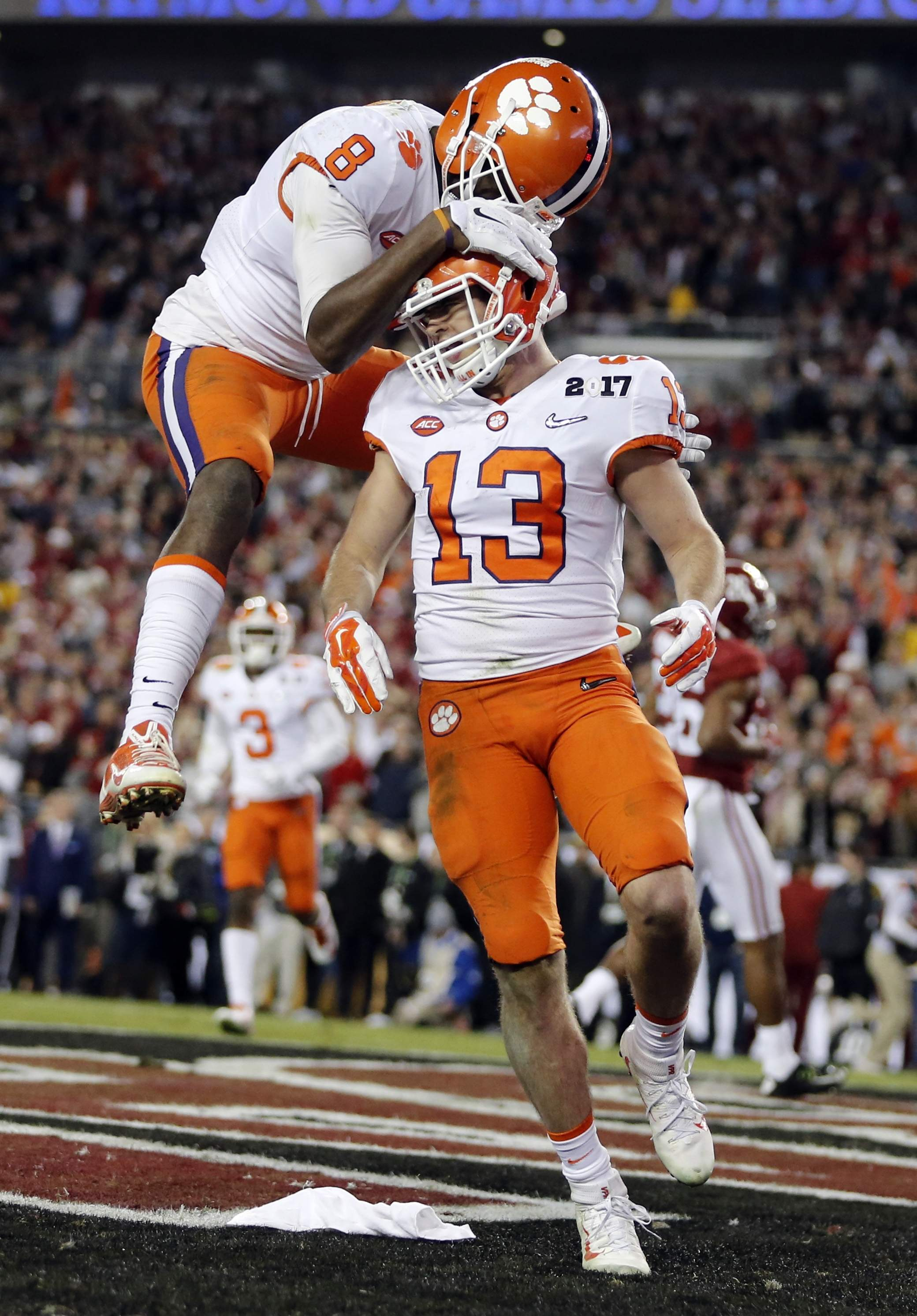 Clemson's Hunter Renfrow is congratulated by teammate Deon Cain after catching a touchdown pass during the second half of the NCAA college football playoff championship game against Alabama Monday, Jan. 9, 2017, in Tampa, Fla. THE ASSOCIATED PRESS
