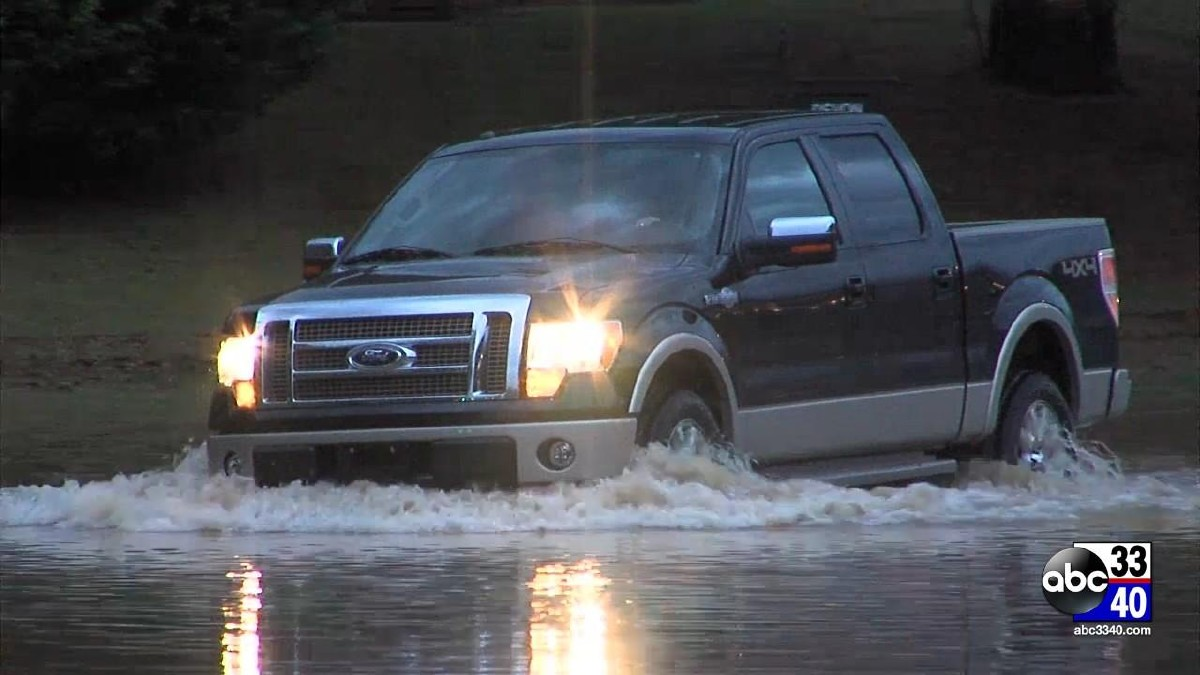 A pickup truck drives through a flooded road in Birmingham, Monday, April 7, 2014.