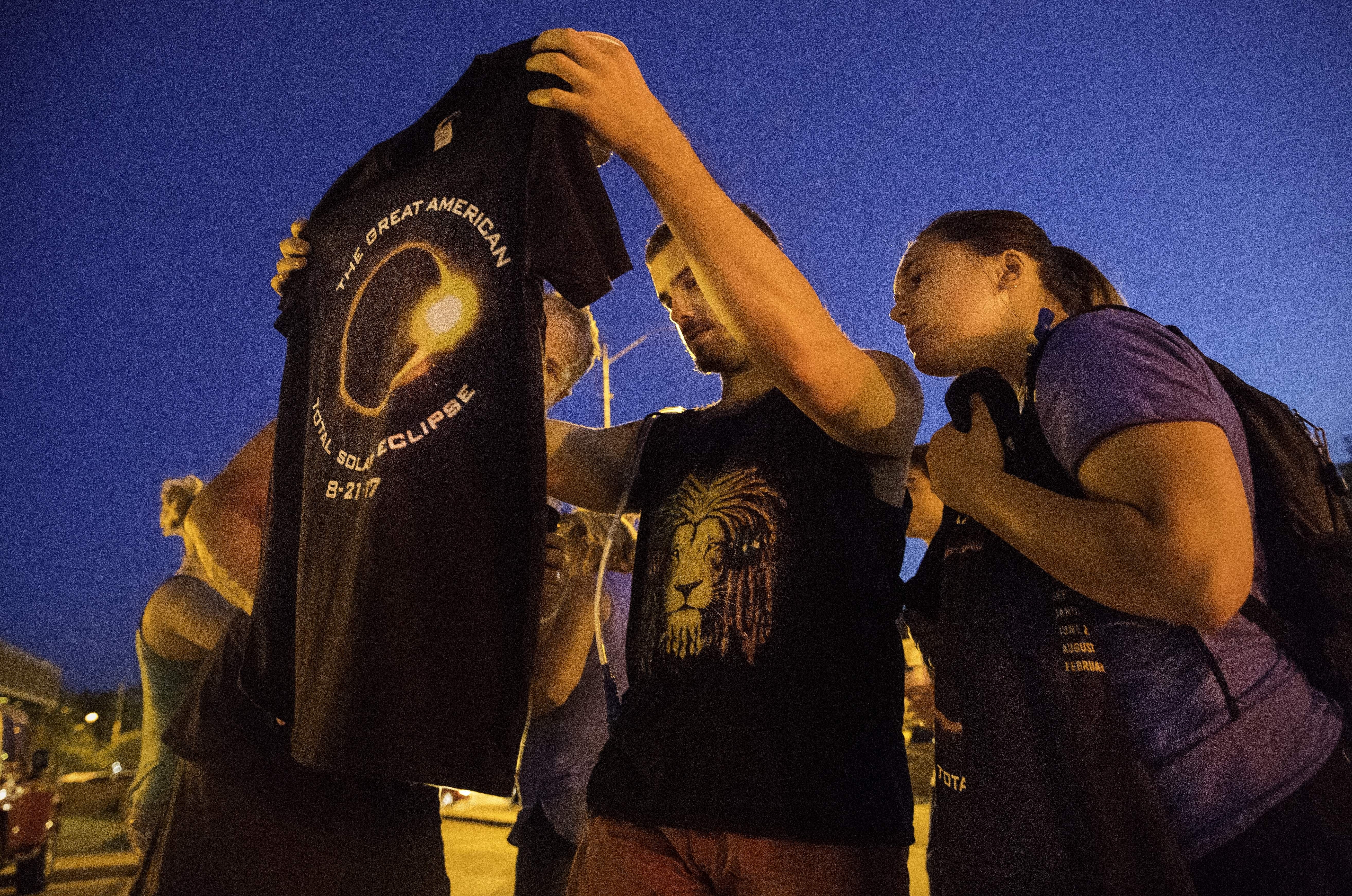 Southern Illinois University Carbondale students Kyle Kruckeberg, left, and Olivia Hajnos inspect their new eclipse t-shirt after picking one up on The Strip Sunday, Aug. 20, 2017. [Ted Schurter/The State Journal-Register]