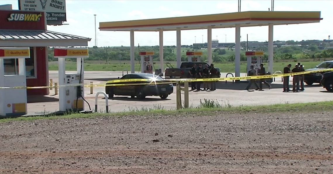 Authorities investigate the scene where a vehicle was reportedly stolen by a man wanted for shooting a Logan County Sheriff's deputy. (KOKH)