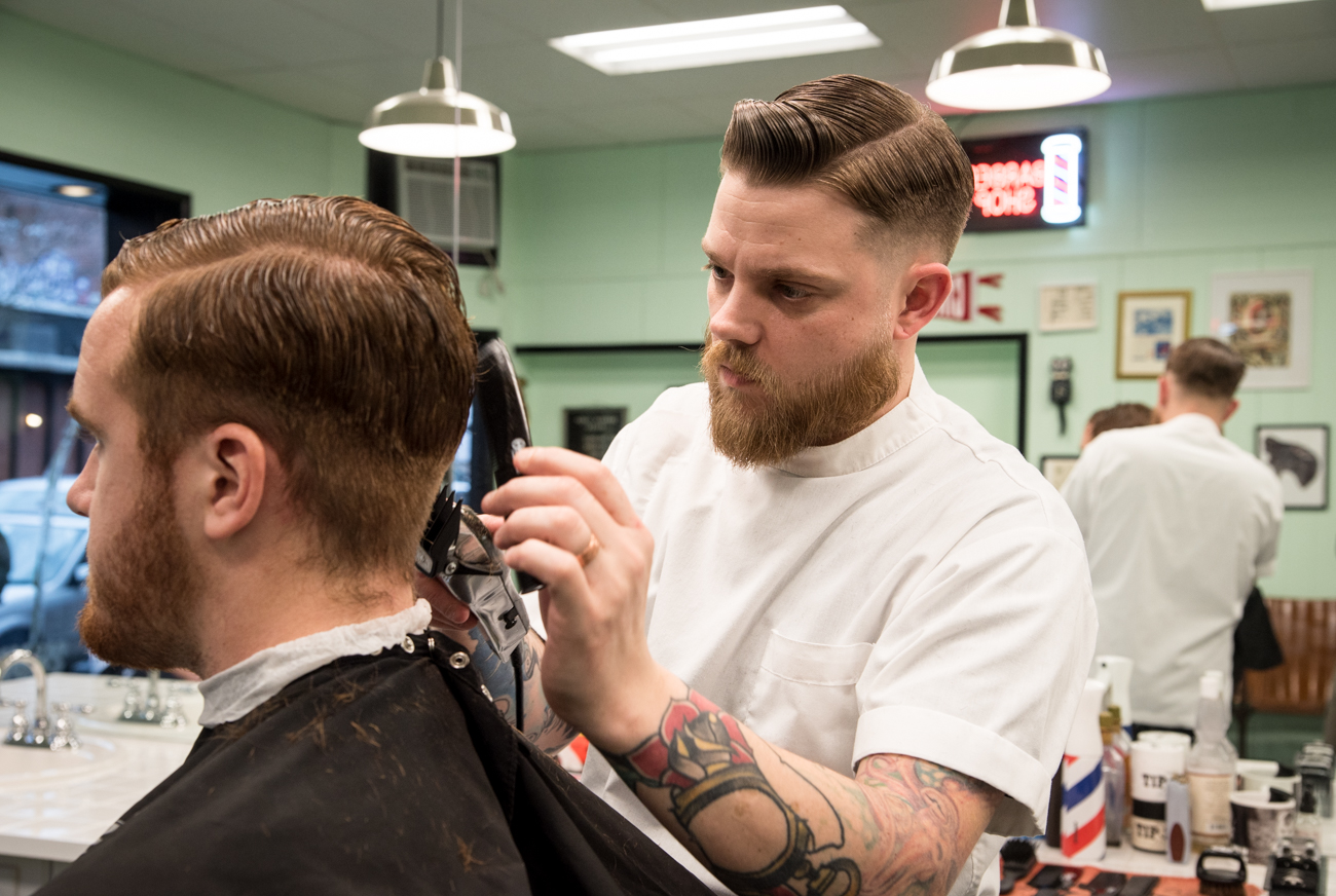 Barber Cody Best works on a customer's haircut at Clifton Barbers. / Image: Melissa Doss Sliney // Published: 3.13.17