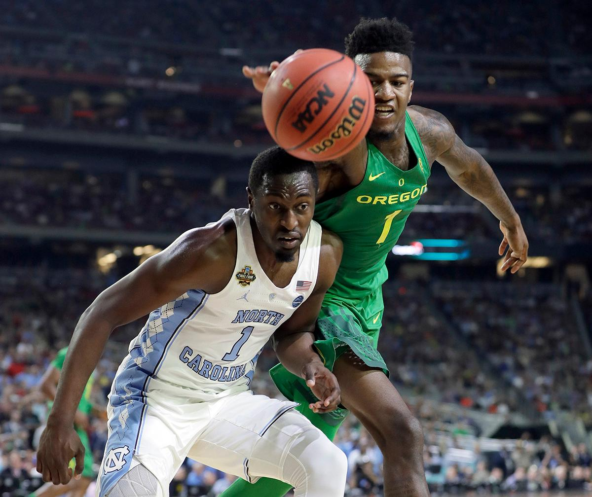 Oregon's Jordan Bell, right, cheese a loose ball against North Carolina's Theo Pinson during the second half in the semifinals of the Final Four NCAA college basketball tournament, Saturday, April 1, 2017, in Glendale, Ariz. (AP Photo/Mark Humphrey)