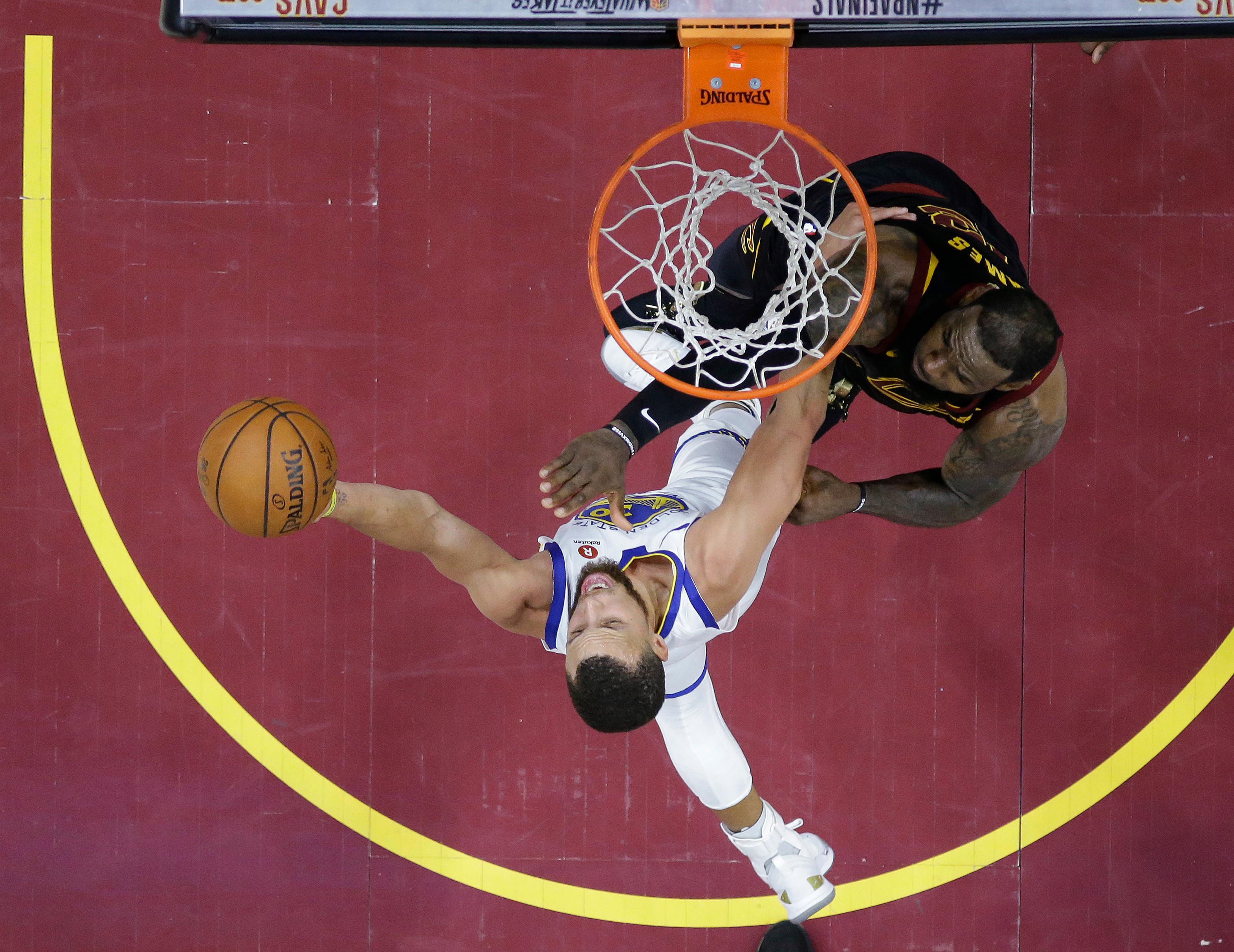 Golden State Warriors' Stephen Curry shoots against Cleveland Cavaliers' LeBron James during the second half of Game 4 of basketball's NBA Finals, Friday, June 8, 2018, in Cleveland. (AP Photo/Carlos Osorio, Pool)