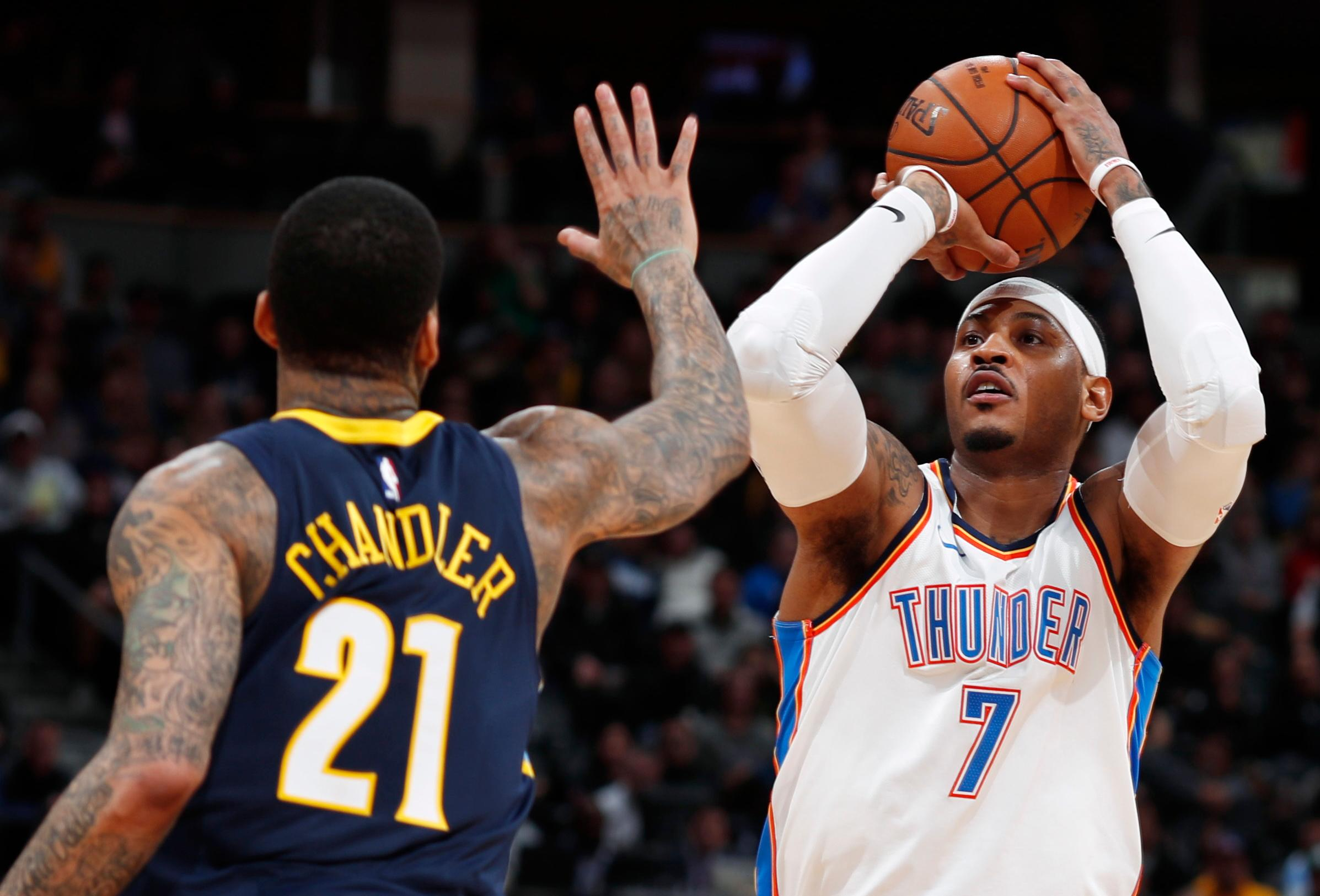 Oklahoma City Thunder forward Carmelo Anthony shoots as Denver Nuggets forward Wilson Chandler defends during the first half of an NBA basketball game Thursday, Feb. 1, 2018, in Denver. (AP Photo/David Zalubowski)