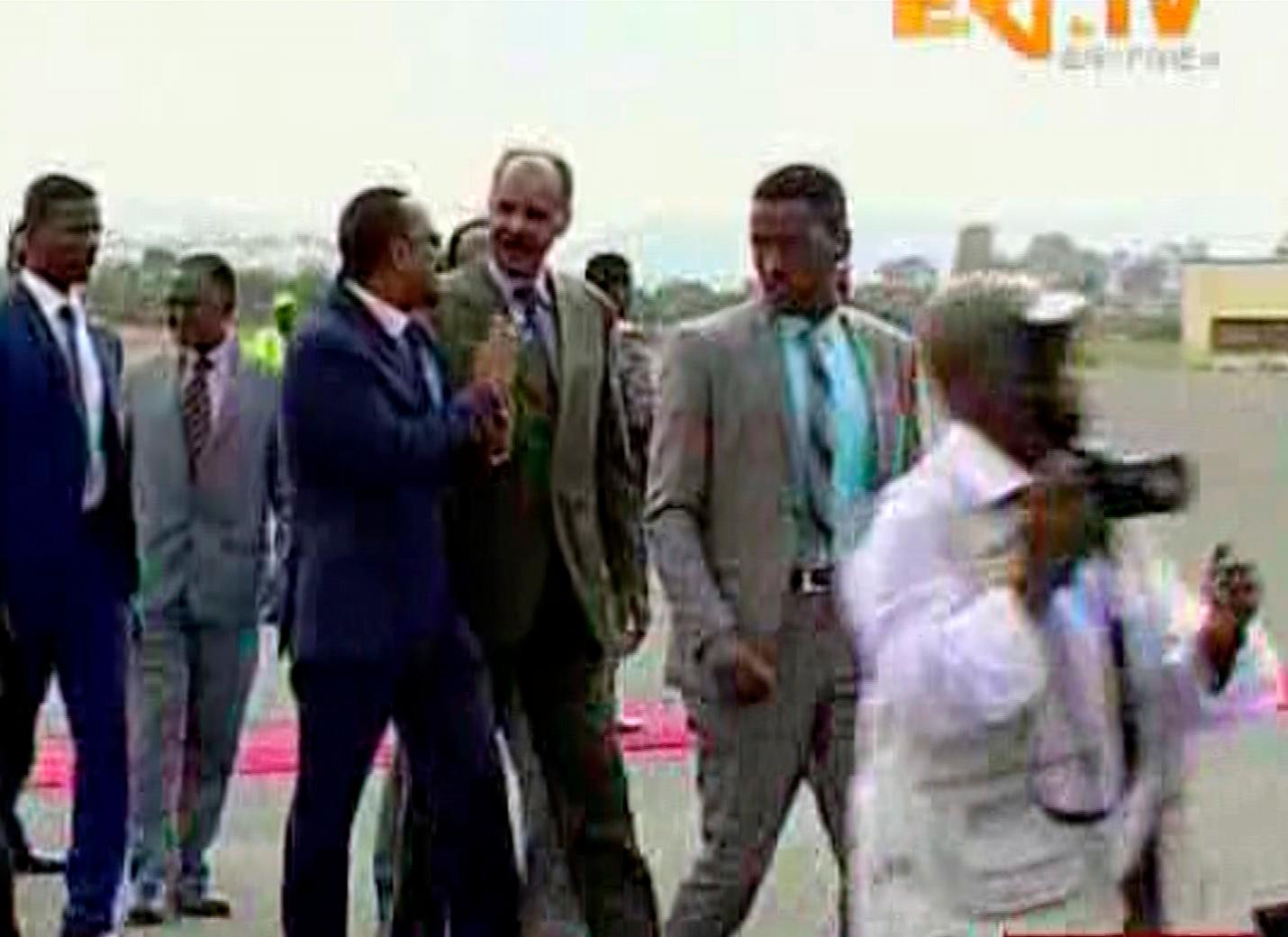 In this grab taken from video provided by ERITV, Ethiopia's Prime Minister Abiy Ahmed, centre left is welcomed by Erirea's President Isaias Afwerki as he disembarks the plane, in Asmara, Eritrea, Sunday, July 8, 2018. With laughter and hugs, the leaders of longtime rivals Ethiopia and Eritrea met for the first time in nearly two decades Sunday amid a rapid and dramatic diplomatic thaw aimed at ending one of Africa's longest-running conflicts. (ERITV via AP)