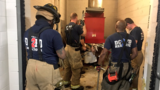 Officials: Firefighters rescue man who fell down trash chute while looking for cellphone