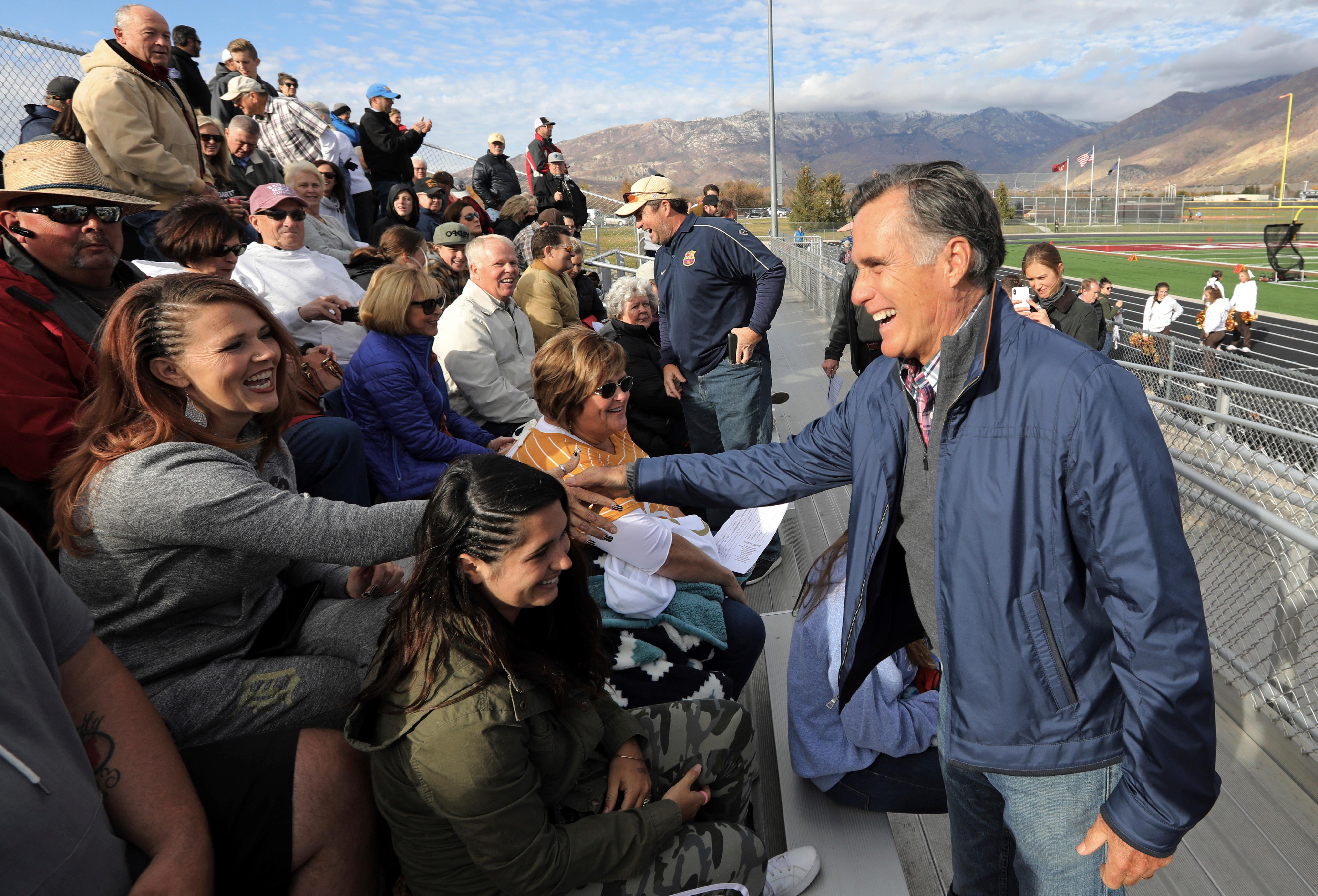 In this Friday, Nov. 2, 2018 photo, former GOP presidential nominee Mitt Romney shakes hands during the Lone Peak High School against Davis High School football game in Highland, Utah. Romney is stumping for fellow Republican candidates as he sails toward a likely victory Tuesday in the race for a U.S. Senate seat from Utah and an official return to public office. (AP Photo/Rick Bowmer)