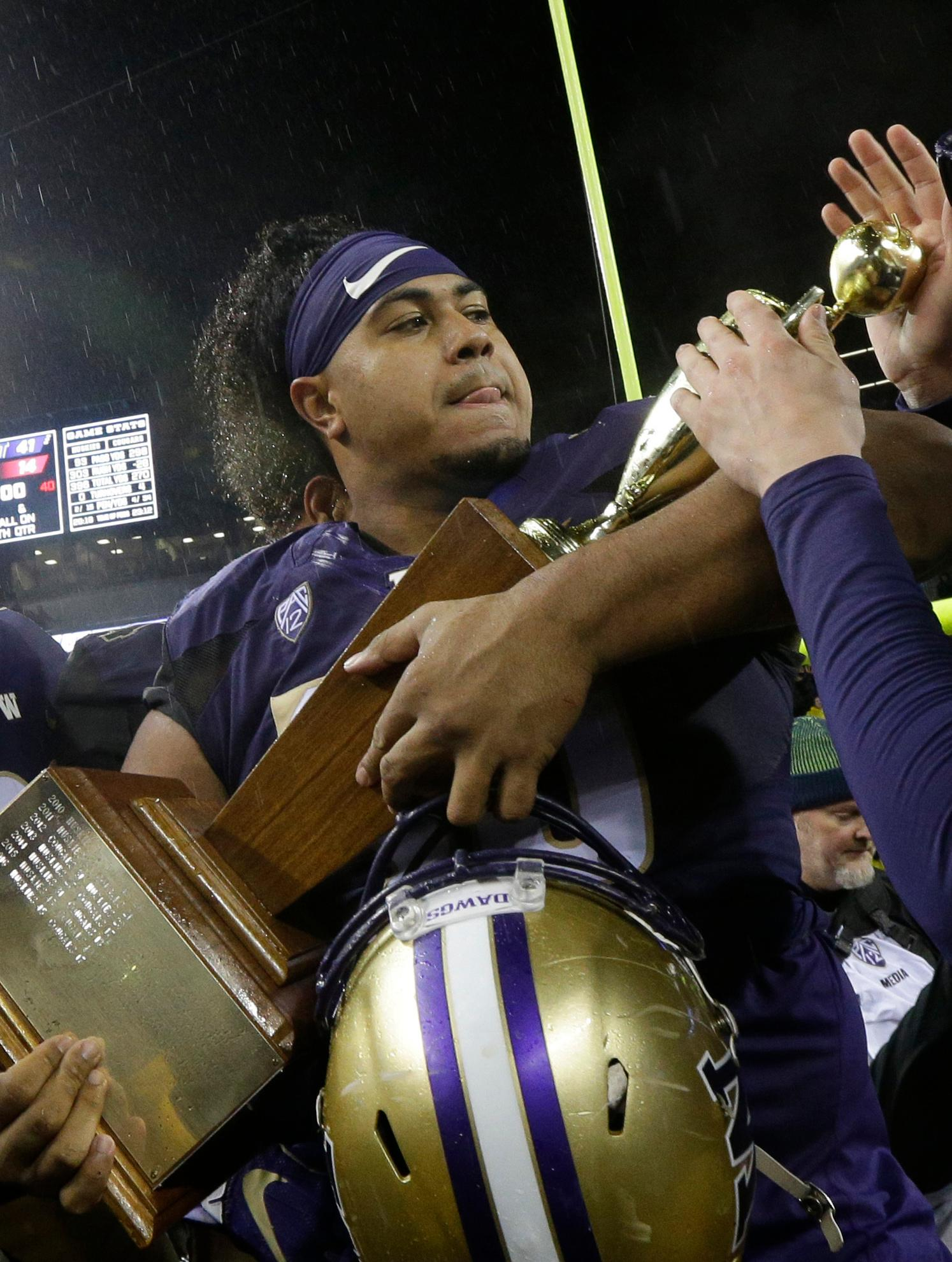 FILE - In this Nov. 25, 2017, file photo, Washington defensive lineman Vita Vea holds the Apple Cup trophy after Washington beat Washington State 41-14 in an NCAA college football game, in Seattle. Vea was selected to the AP All-Conference Pac-12 team announced Thursday, Dec. 7, 2017. (AP Photo/Ted S. Warren, File)