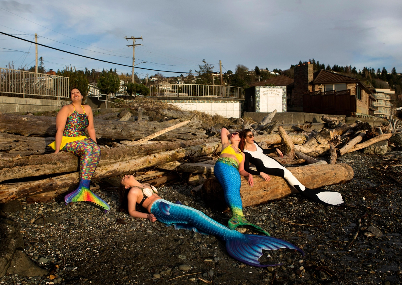 "(Left to right) LeAnne Gatlin, Brianna Parise, Emily Beckley, and Jamie Von Stratton take in some sun as they lay on driftwood at Charles Richey Sr. Viewpoint. The four are part of the Seattle Mermaids, which is ""...a collective of mermaids, mermen, and mer friends who love the magic of Merm Lyfe."" (Sy Bean / Seattle Refined)"