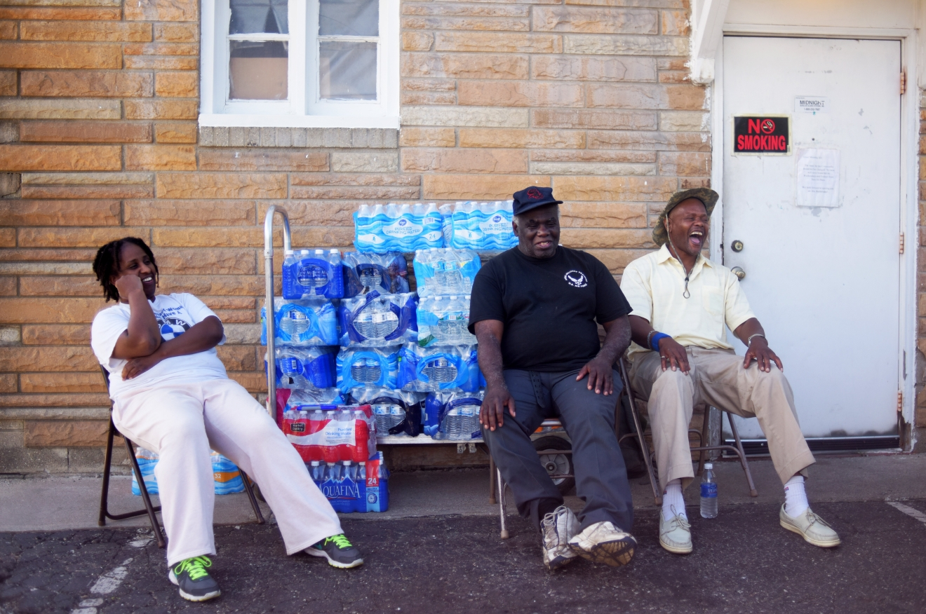 "Stephanie Smith, left, Jimmie Thompson, center, and Otis Ross, right, share a laugh in-between residents coming to get water at Prince of Peace Baptist Church Wednesday, June 22, 2016 in northwest Flint. Every Monday, Wednesday and Friday the church gives out water for free from 10 a.m. to 2 p.m. ""My brother lives in Atlanta. I try to tell him he doesn't realize how bad the water crisis is here,"" Ross said. ""You can't imagine it until you get here."" (Mark Felix/The Flint Journal-MLive.com via AP) LOCAL TELEVISION OUT; LOCAL INTERNET OUT; MANDATORY CREDIT"
