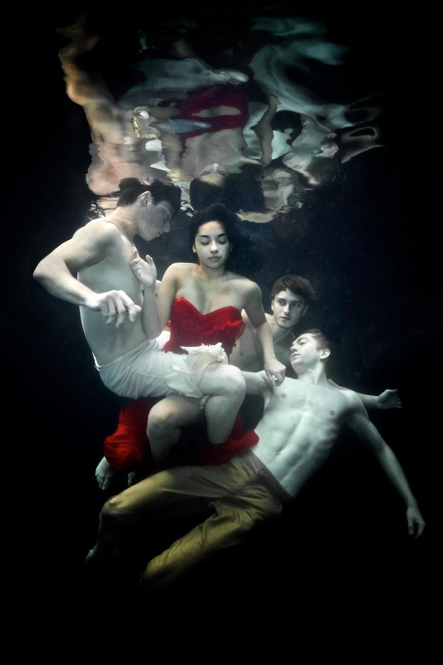 "Statement from artist Tina Gutierrez: ""In this underwater series, a watery environment invites the dancers to yield to the embrace of liquid instead of the greater forces of gravity that they normally experience. The added difficulty of working in the water creates a world of unexpected challenges for the dancer and the photographer. These images are only viewable from below the water and are so fleeting that they can only be captured by the speed of the camera. Due to its calmness yet danger, the water for me has always been a place of peace and solace yet also extreme awareness. The need to make these images is beyond explanation, perhaps as I believe the end result appeals to a deep primal elemental need. Most of the dancers are from the Cincinnati Ballet."" / Cincinnati Ballet B company dancers Quinn Barrett, Jimena Flores Sanchez, Daniel Kuber, and Ethan Kimbrell / Image: Tina Gutierrez // Published: 3.28.20<br><p></p>"