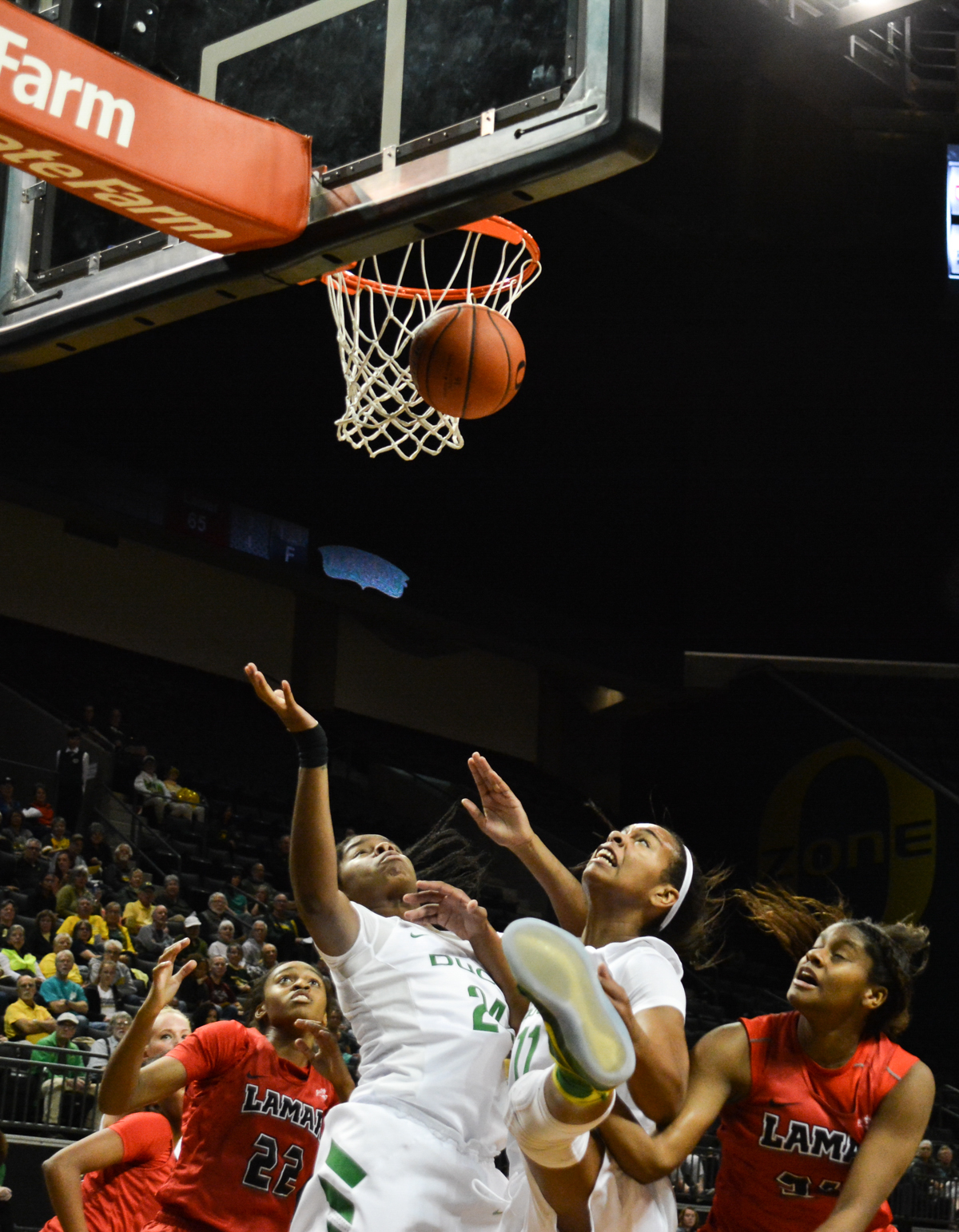 Ducks Jayde Woods (#11) and Ruthy Hebard (#24) battle with two Cardinal defenders over a rebound. The Oregon Ducks women's basketball team won their season opener against the Lamar Cardinals 84-67. Photo by Jacob Smith, Oregon News Lab