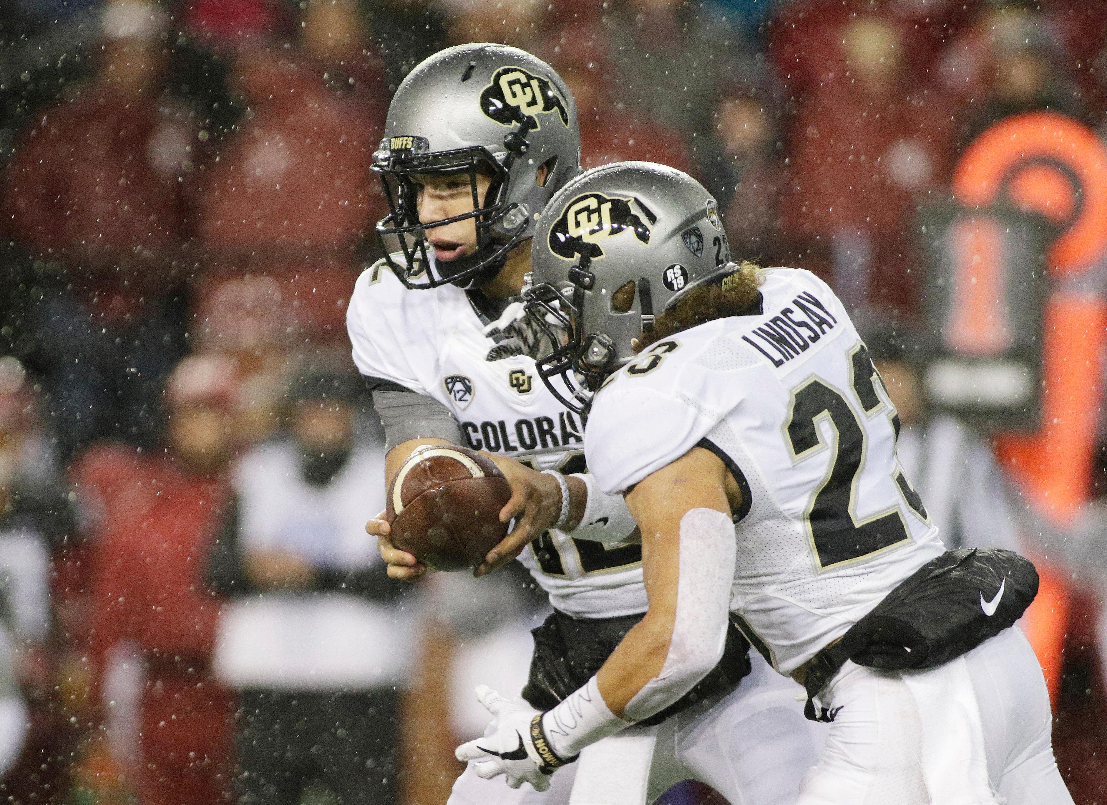Colorado quarterback Steven Montez, left, hands the ball off to running back Phillip Lindsay (23) during the first half of an NCAA college football game against Washington State in Pullman, Wash., Saturday, Oct. 21, 2017. (AP Photo/Young Kwak)