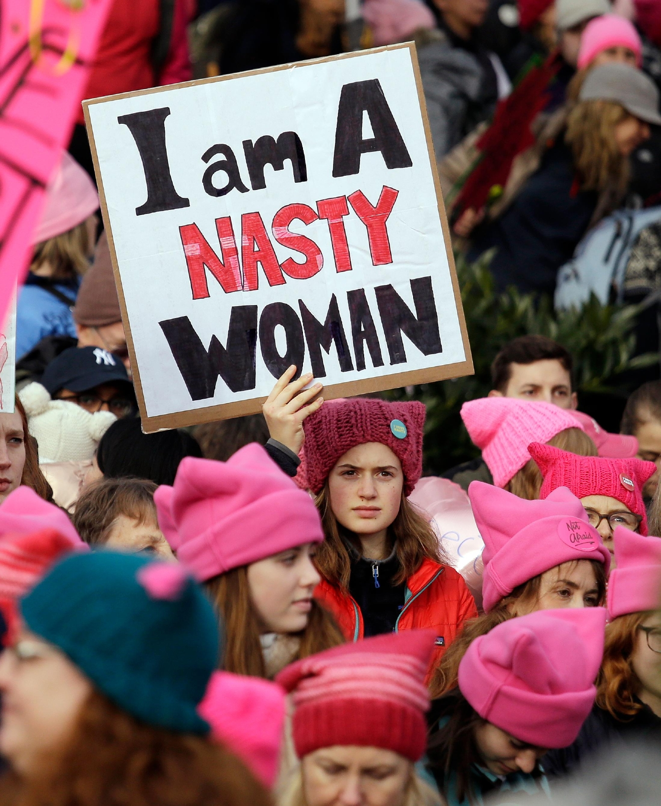 A woman holds a sign amidst a sea of pink caps before a women's march Saturday, Jan. 21, 2017, in Seattle. Women across the Pacific Northwest marched in solidarity with the Women's March on Washington and to send a message in support of women's rights and other causes. (AP Photo/Elaine Thompson)