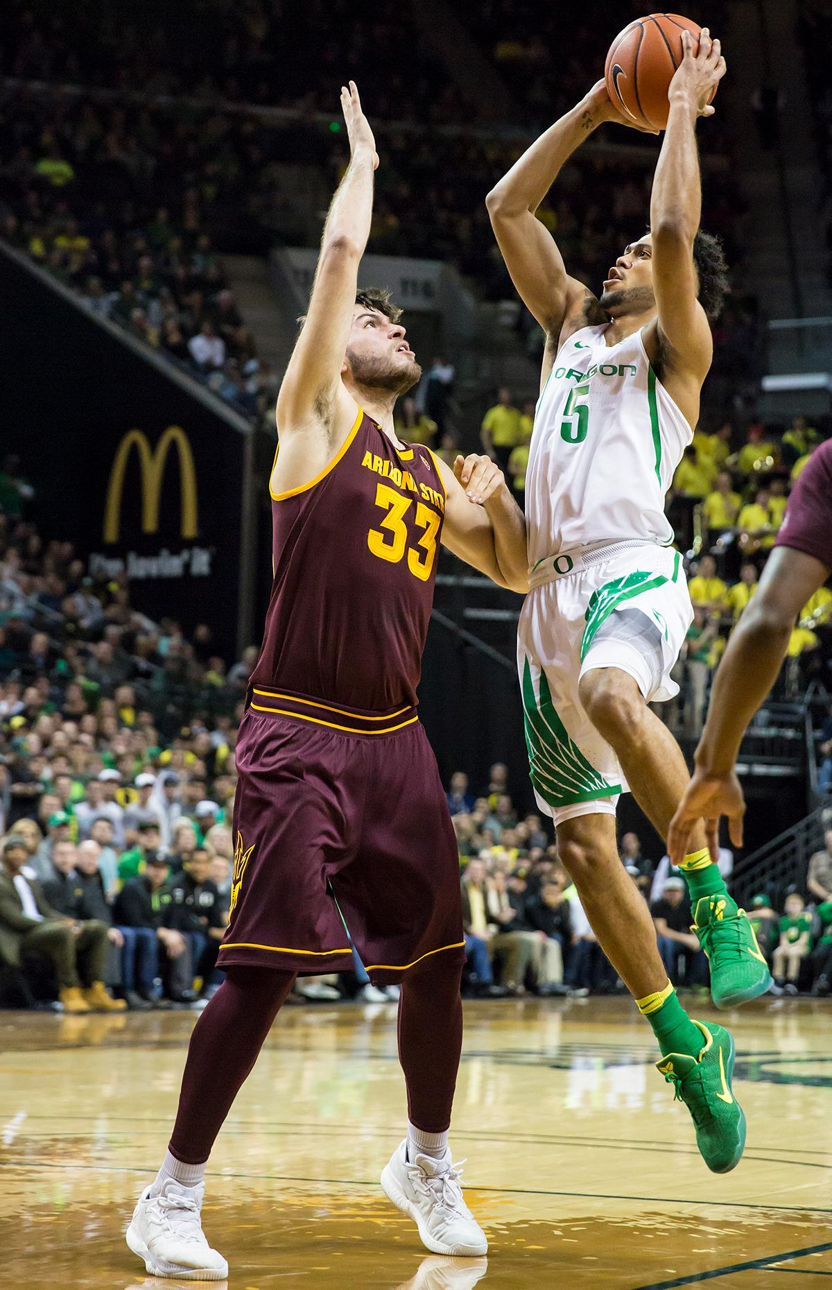 Oregon guard Tyler Dorsey (#5) leaps over Arizona State forward Roman Vila (#33) and towards the basket. The Oregon Ducks defeated the Arizona State Sun Devils 71 to 70. Photo by Ben Lonergan, Oregon News Lab