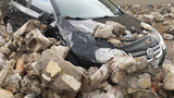 Reinforced rock wall collapses; businesses and vehicles damaged