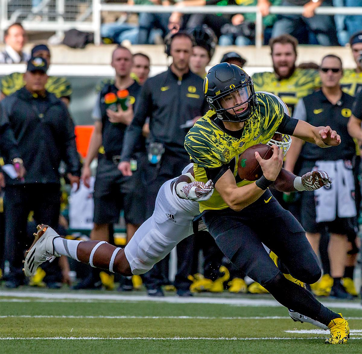 The Duck's Justin Herbert (#10) runs the ball down the field. The Oregon Ducks broke their losing streak by defeating the ASU Sun Devils on Saturday 54-35. Photo by August Frank, Oregon News Lab