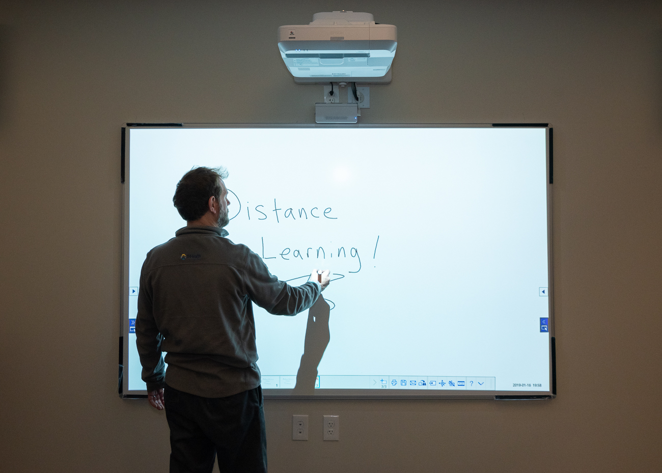 Rodger Pille uses the smart board in the classroom. The device overhead acts as a digital overhead projector, allowing the information to be beamed to any classroom in the world sharing the feed. / Image: Phil Armstrong, Cincinnati Refined // Published: 1.26.19
