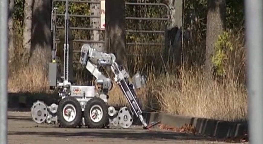 October 5, 2017: The larger robot took the device to another location and appeared to be manipulating it to allow explosives technicians to examine the device. The bomb squad determined that what initially appeared to be dynamite and a cell phone was actually road flares and a recording device taped together. (SBG)<p></p>
