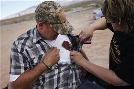 Krissy Thornton, right, looks at blood from a taser wound on Ammon Bundy near Bunkerville, Nev. Wednesday, April 9, 2014.