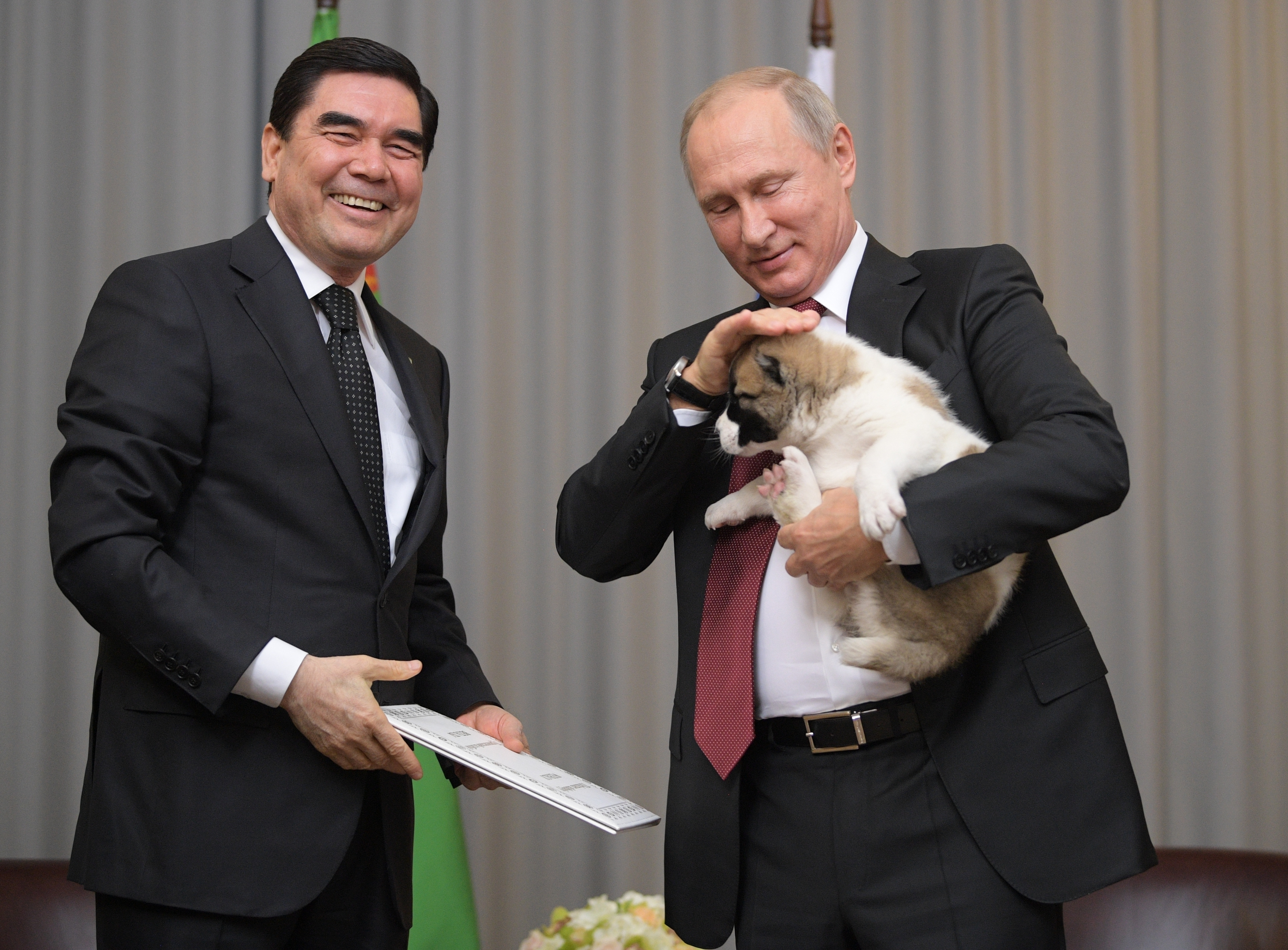 Turkmenistan's President Gurbanguly Berdymukhamedov, right, smiles as he presents a puppy to Russian President Vladimir Putin during their meeting in the Bocharov Ruchei residence in the Black Sea resort of Sochi, Russia, Wednesday, Oct. 11, 2017. The presidents met on the sidelines of a summit of leaders of ex-Soviet nations in Sochi. (Alexei Druzhinin/Sputnik, Kremlin Pool Photo via AP)