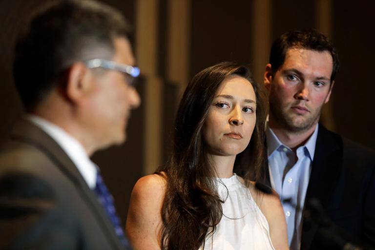 Olympic swimmer Ariana Kukors Smith, center, stands with her husband, Matt Smith, right, as they listen to Ray Mendoza, left, a member of her investigative team, as he talks to reporters, Monday, May 21, 2018, during a news conference in Seattle. Kukors Smith sued USA Swimming on Monday, alleging the sport's national governing body knew her former coach sexually abused her as a minor and covered it up. (AP Photo/Ted S. Warren)