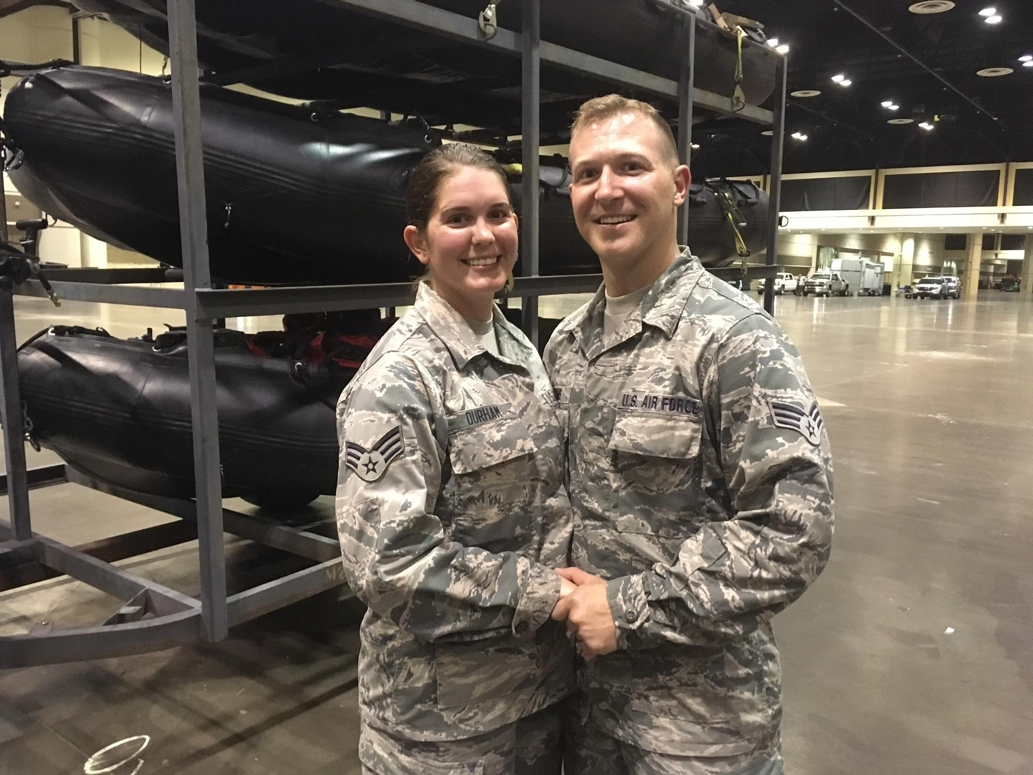 Lauren Durham, left, and Michael Davis, both members of the Air National Guard, pose at the Orange County Convention Center in Orlando, Fla., on Sunday, Sept. 10, 2017. The couple were planning to get married on a beach next weekend but were deployed to assist in the relief efforts for Hurricane Irma. Instead they got married Sunday in fatigues in a vast hangar filled with rescue vehicles and paramedics.  (AP Photo/Claire Galofaro)