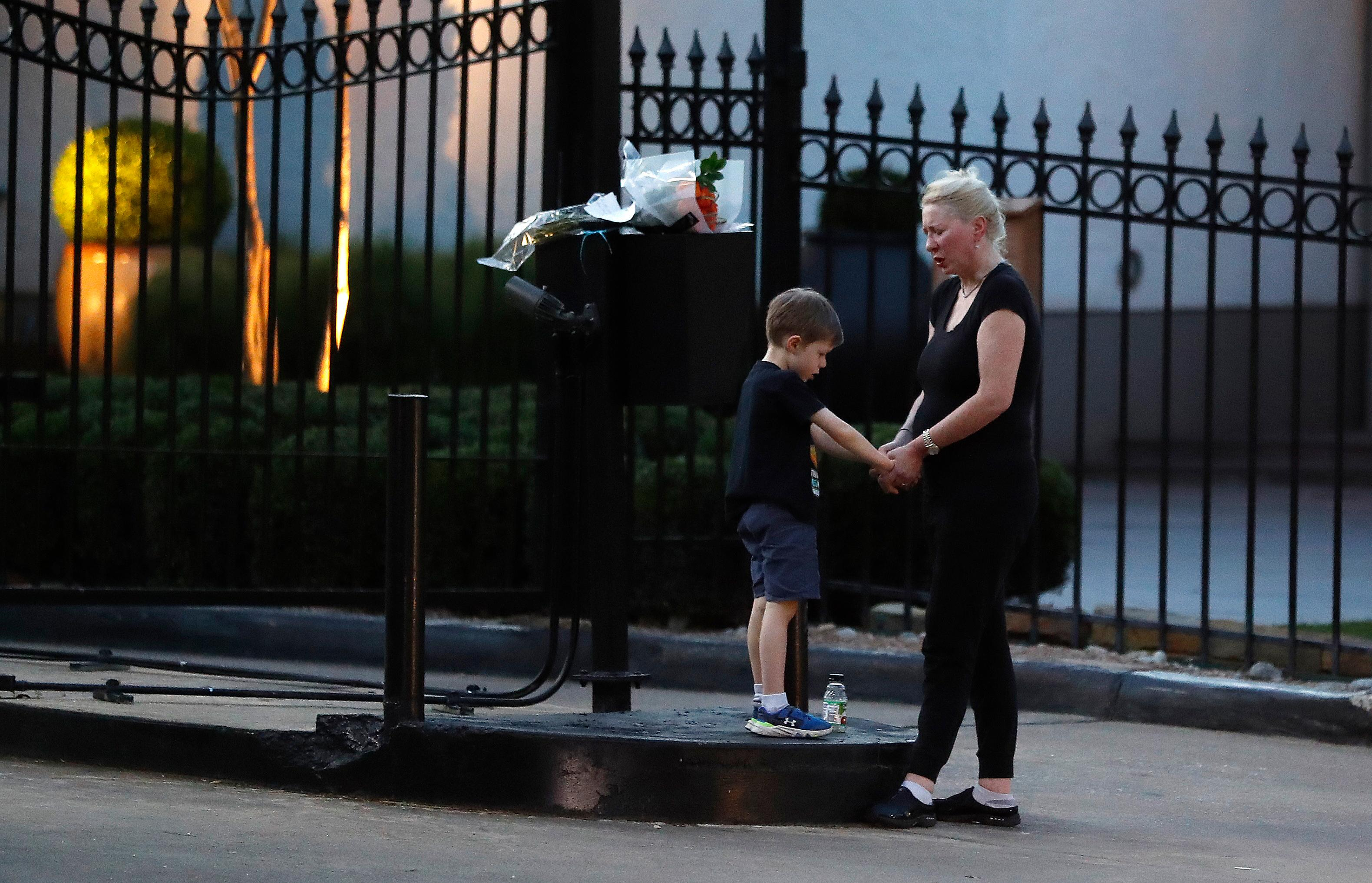 "Amanda Gross holds the hands of her 6-year-old son, Patrick Henry, as they pray outside of the gated community where former first lady Barbara Bush died earlier in the day, Tuesday, April 17, 2018, in Houston. ""Since he was in my womb, I have read him stories about more first ladies than presidents,"" Gross said. ""Barbara Bush was the appropriate political figure. She will be missed,"" said Gross. (Karen Warren/Houston Chronicle via AP)"