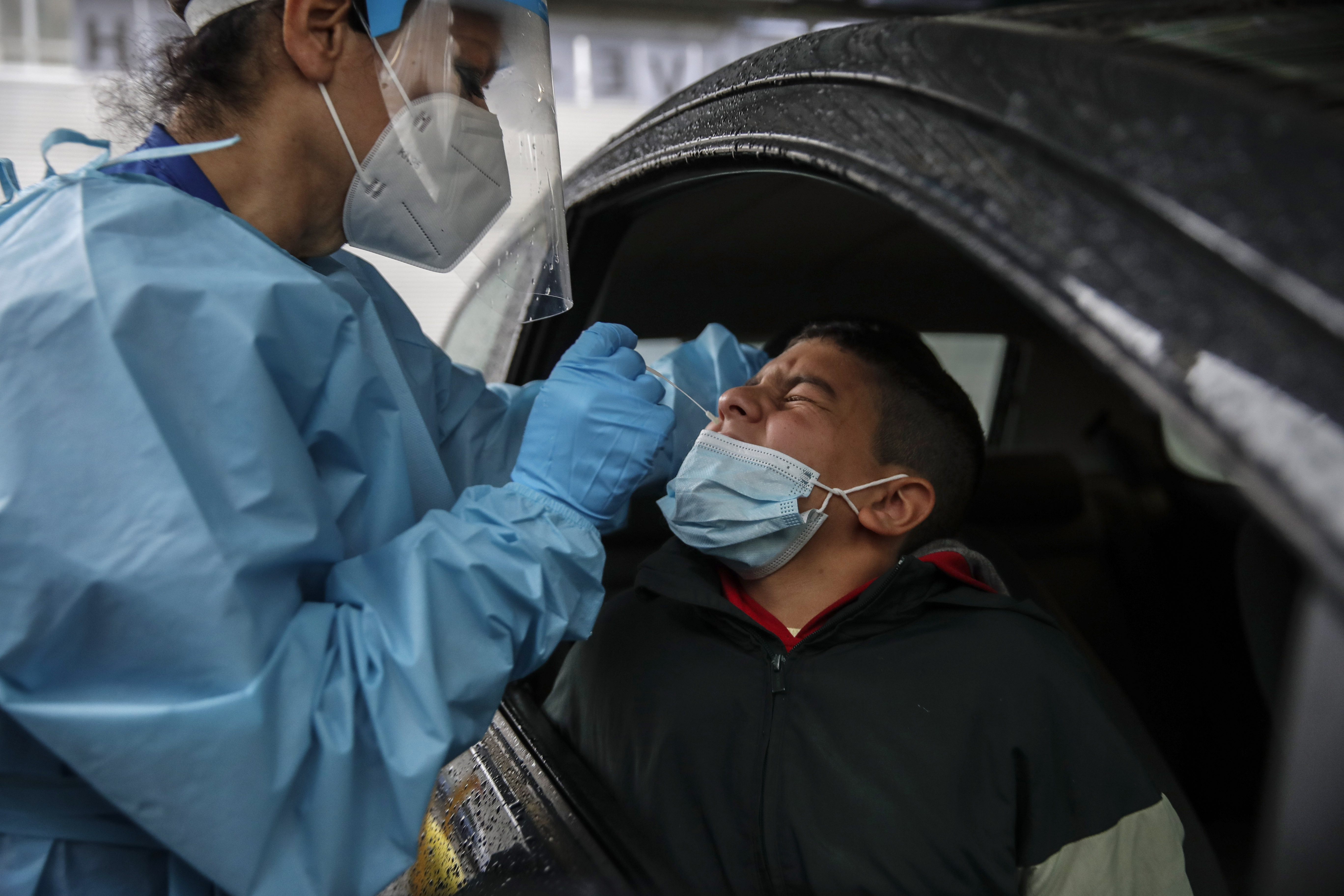 Medical staff takes a swabs as she tests a boy for COVID-19 at a drive-through at the San Paolo hospital, in Milan, Italy, Thursday, Oct. 15, 2020. Coronavirus infections are surging again in the region of northern Italy where the pandemic first took hold in Europe, renewing pressure on hospitals and health care workers. (AP Photo/Luca Bruno)