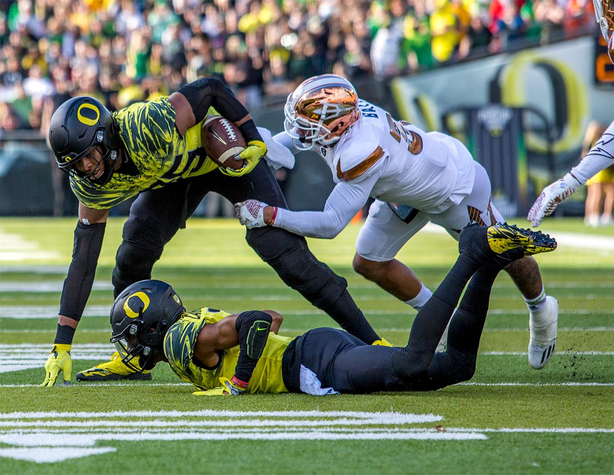 The Duck's Pharaoh Brown (#85) keeps his eyes on the end zone as a Sun Devils player attempts to bring him down. Oregon lead at the end of the 1st half 30-14. Photos by August Frank, Oregon News Lab