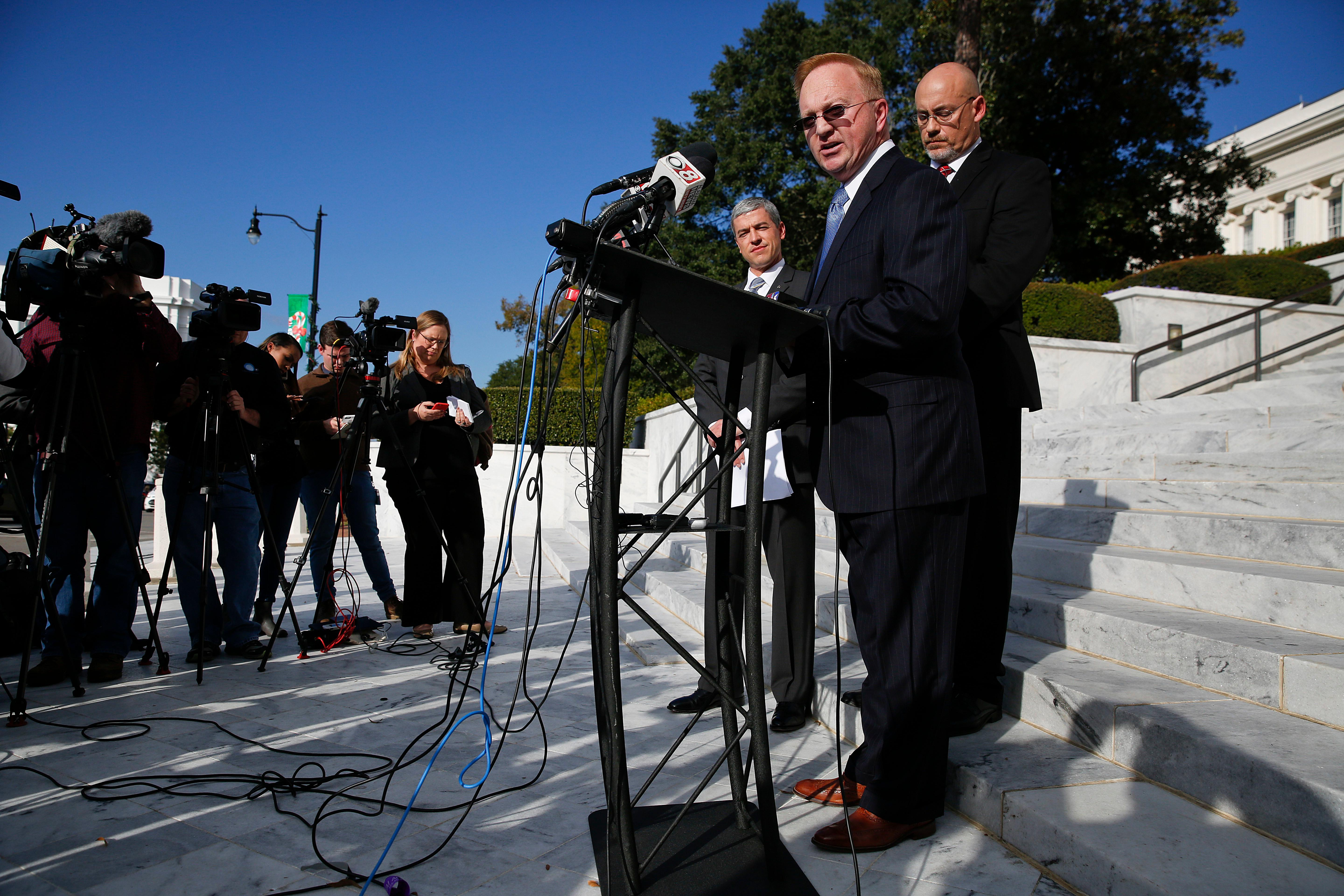 Stan Cooke, center, a member of former Alabama Chief Justice and U.S. Senate candidate Roy Moore's campaign, speaks at a news conference, Tuesday, Nov. 21, 2017, in Montgomery, Ala. (AP Photo/Brynn Anderson)