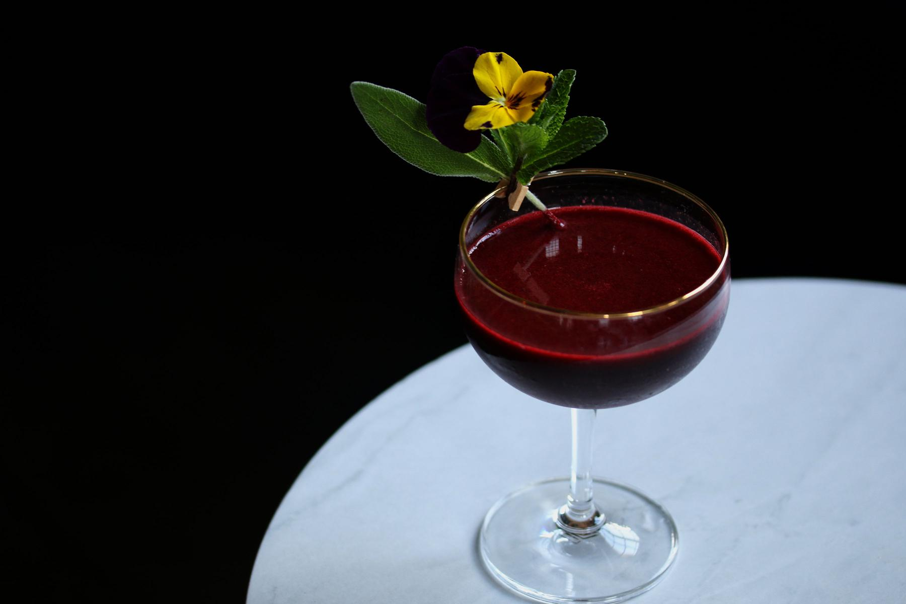 "Blooms of Spring: An exotic beet molasses cocktail, also uses Chopin Rye Vodka, Green Chartreuse and Persian lime. ""Cold Winter views and his realms of snow, Delaney's vegetable statues blow, smooths his stern brow, delays his hoary wing, and eyes with wonder all the blooms of spring."" (Image: Jai Williams)"