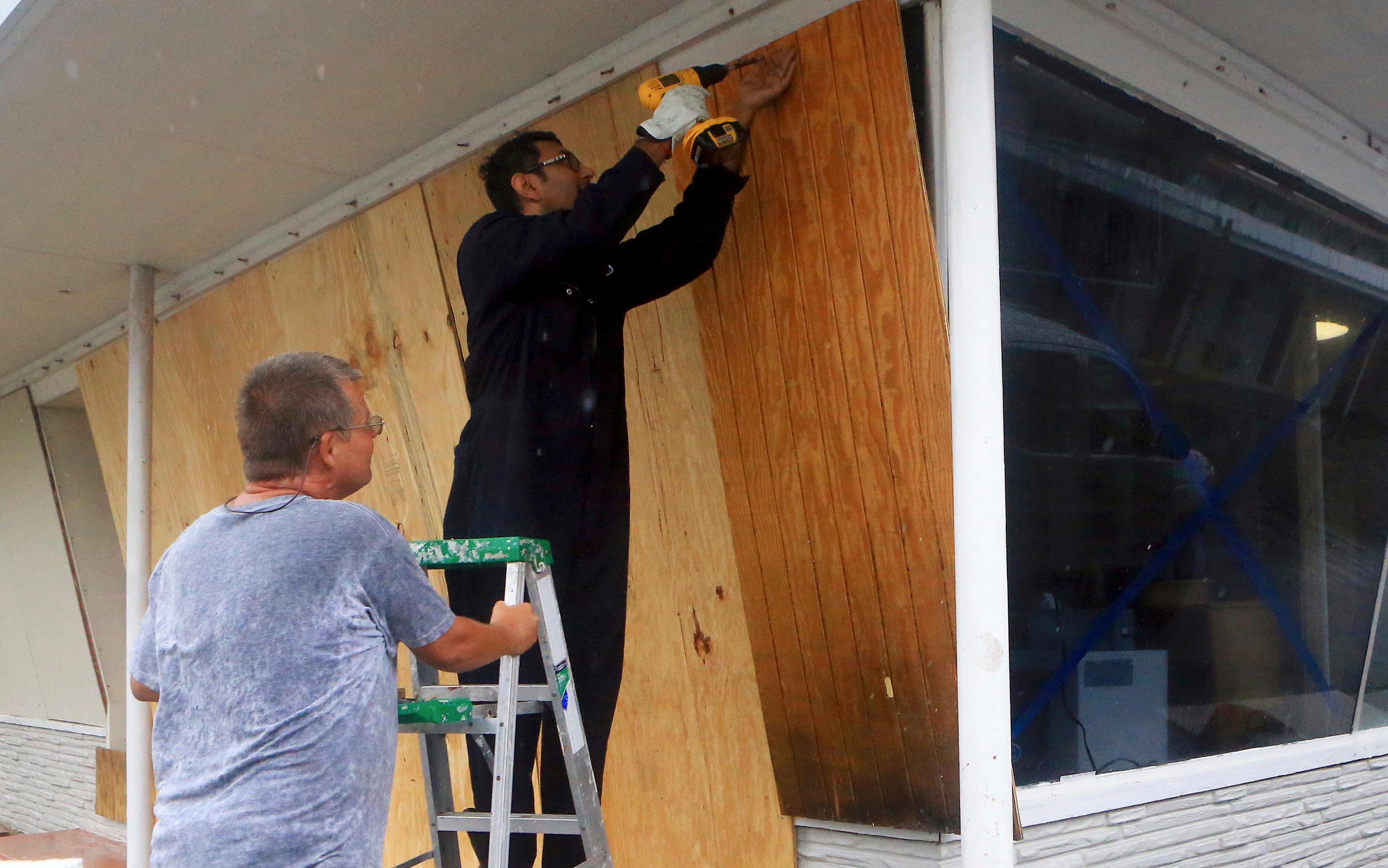 Vimal Patel  boards up windows with the help of Carl Bledsoe (left)  at the Catalina Motel as Hurricane Harvey approaches the Coastal Bend area on Friday, Aug. 25, 2017, in Corpus Christi, Texas. The National Hurricane Center warns that conditions are deteriorating as Hurricane Harvey strengthens and slowly moves toward the Texas coast. (Gabe Hernandez/Corpus Christi Caller-Times via AP)