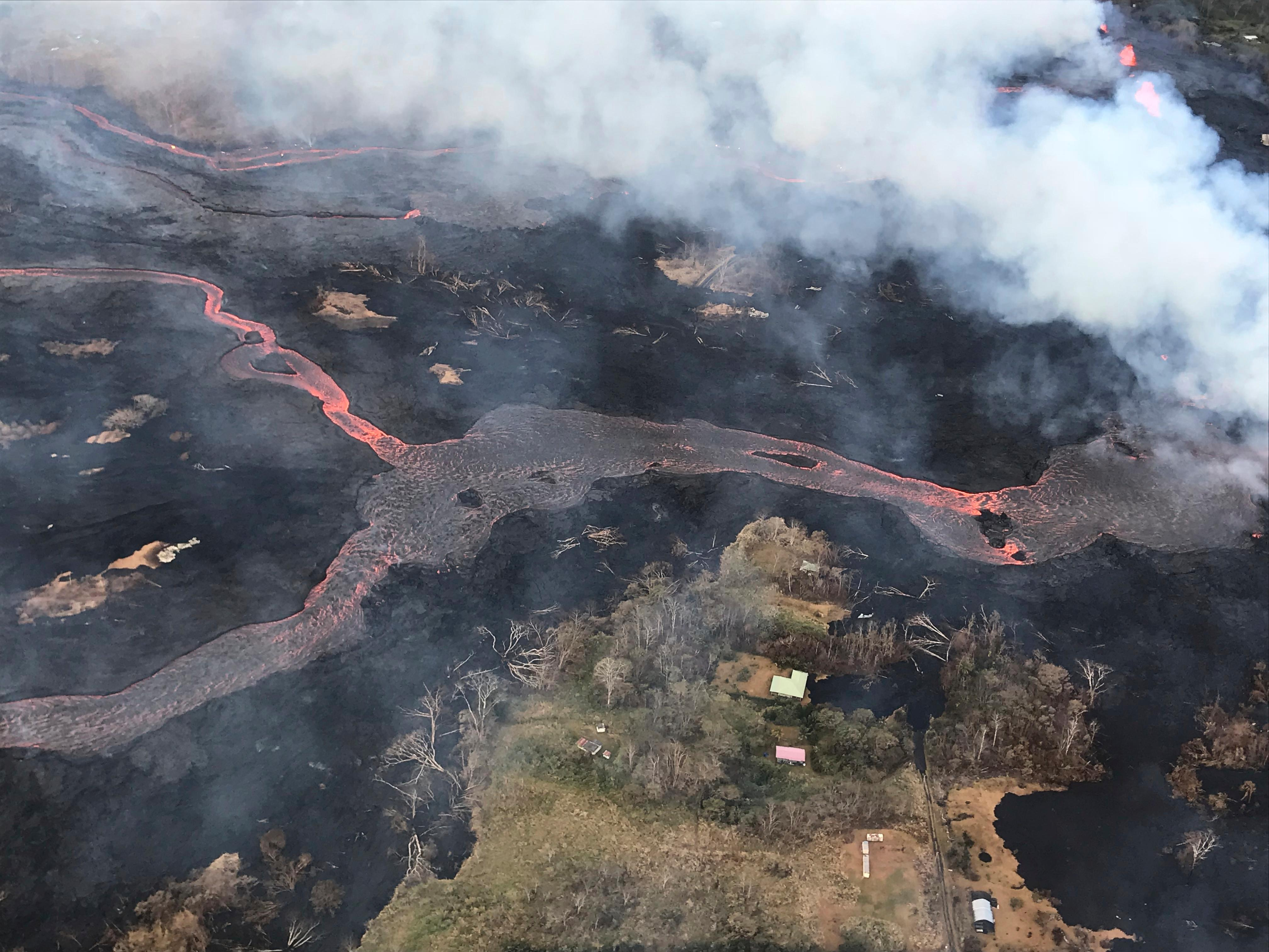 This Wednesday, May 23, 2018 photo shows a helicopter overflight of K?lauea Volcano's lower East Rift Zone near Pahoa, Hawaii.   The volcano produces methane when hot lava buries and burns plants and trees. Scientists say the methane can seep through cracks several feet away from the lava. ( U.S. Geological Survey via AP)