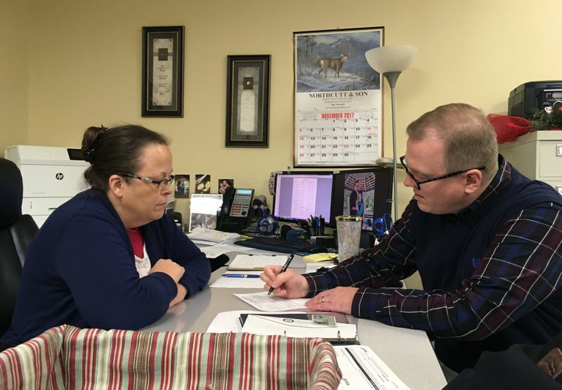 David Ermold, right, files to run for Rowan County Clerk in Kentucky as Clerk Kim Davis looks on Wednesday, Dec. 6, 2017, in Morehead, Ky. Davis denied Ermold and his husband a marriage license two years ago because she was opposed to gay marriage for religious reasons. (AP Photo/Adam Beam){&amp;nbsp;}<p></p>