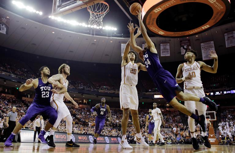 TCU guard Kenrich Williams (34) drives to the basket past Texas forward Jericho Sims (20) during the first half of an NCAA college basketball game Wednesday, Jan. 10, 2018, in Austin, Texas. (AP Photo/Eric Gay)
